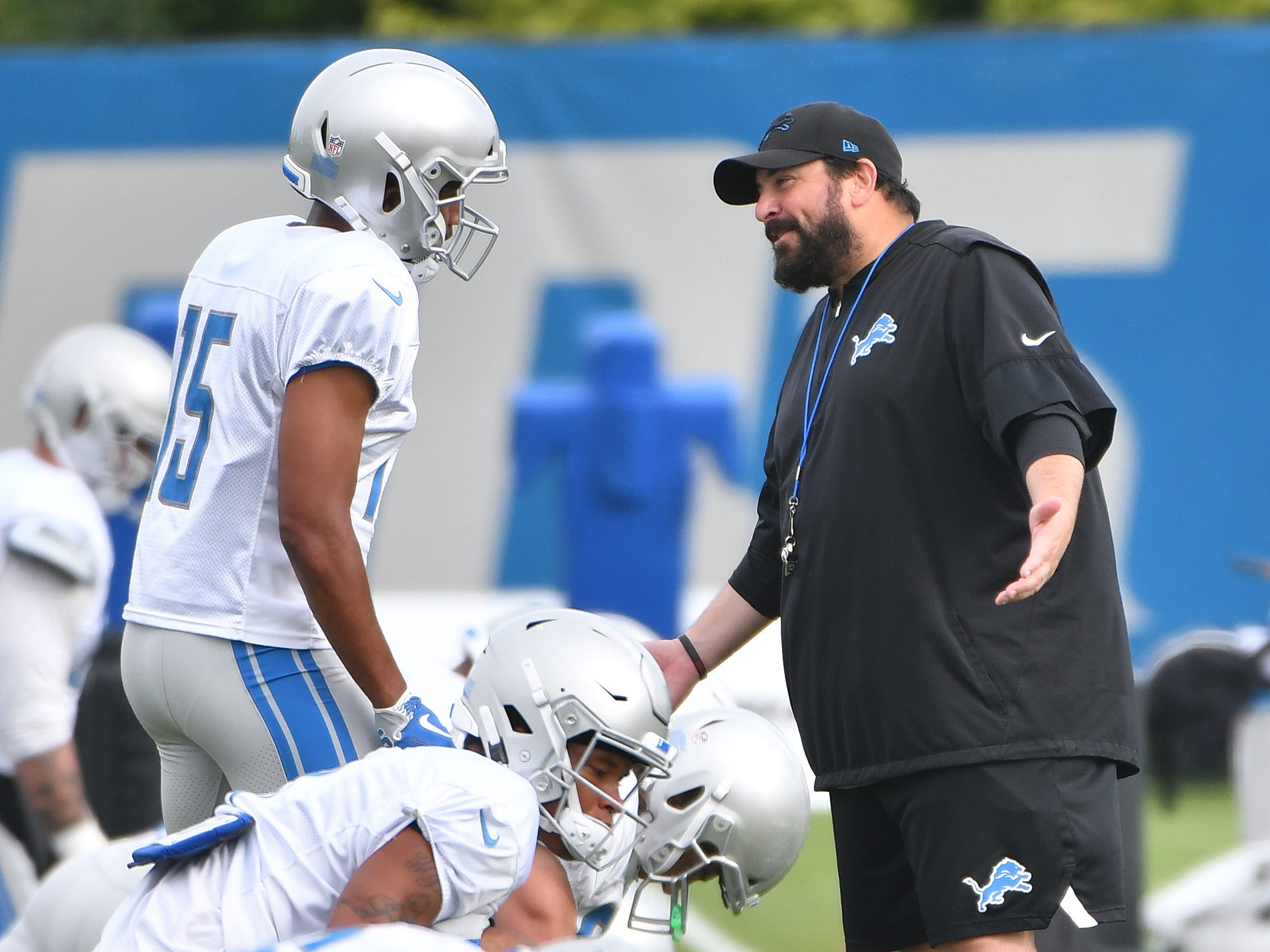 Lions head coach Matt Patricia chats wide receiver Golden Tate as he and the team go through stretching early Wednesday morning at training camp.
