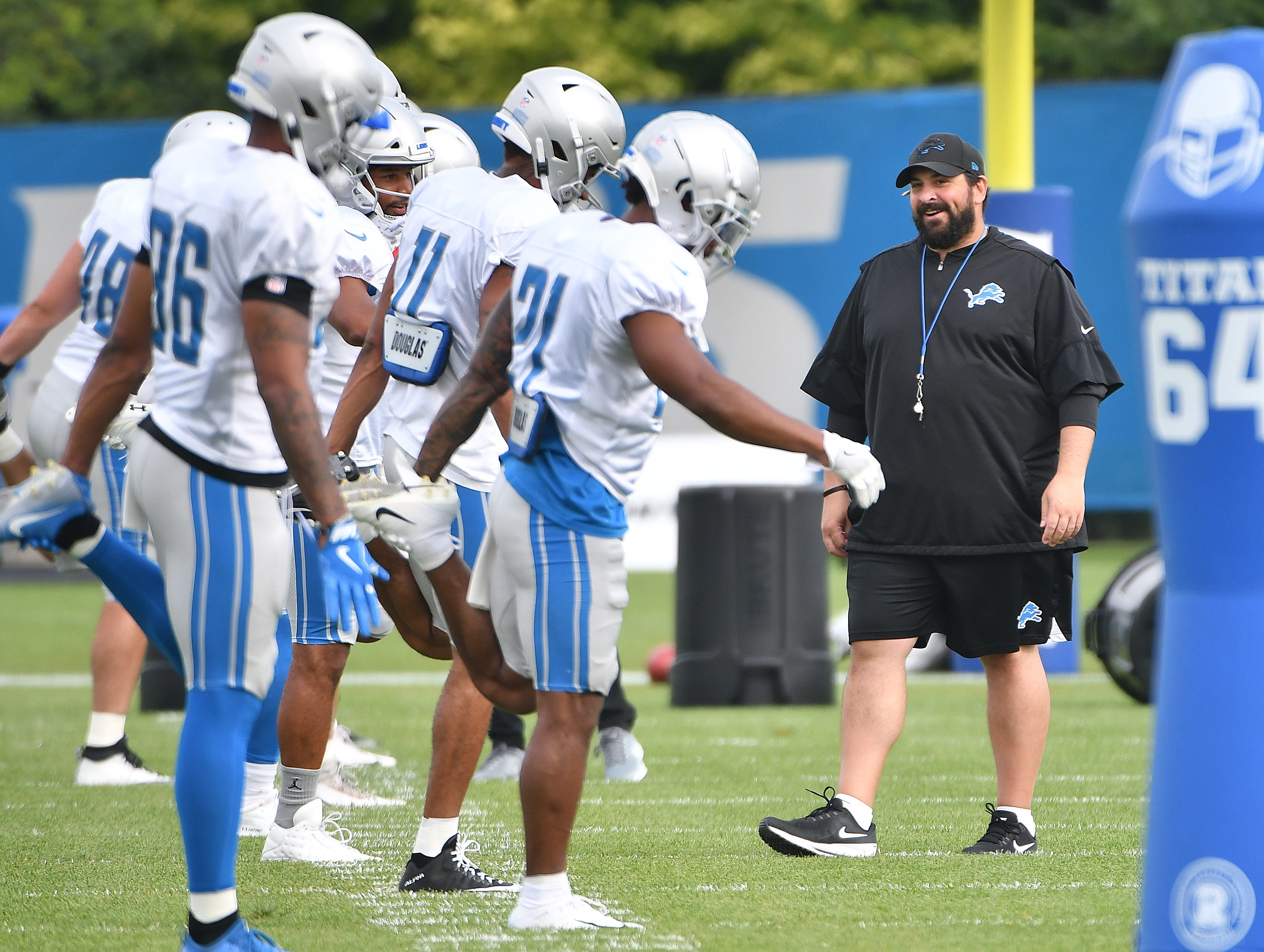 Lions head coach Matt Patricia chats with players as they go through stretching early Wednesday morning at training camp.