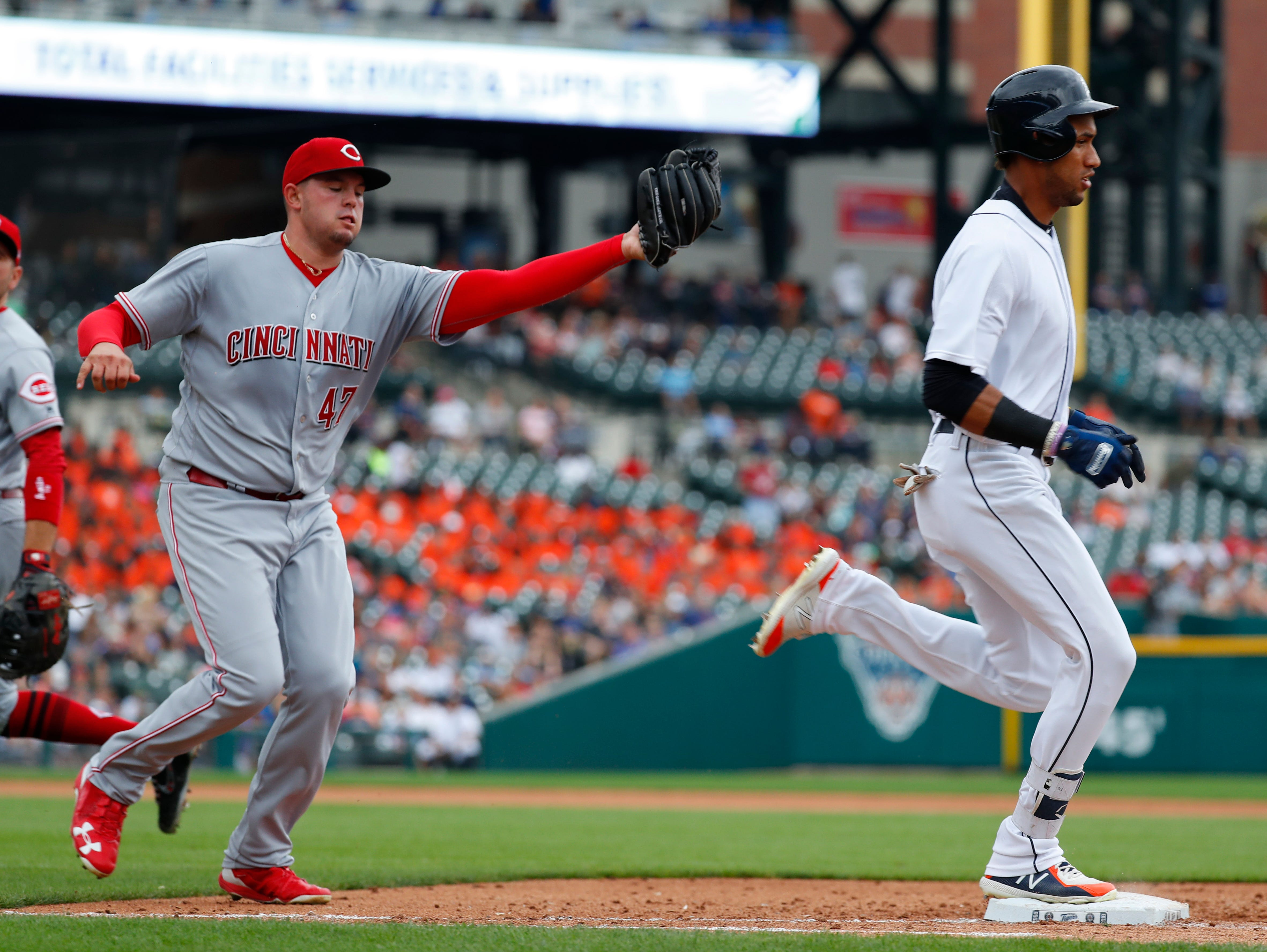 The Tigers' Victor Reyes beats Cincinnati Reds pitcher Sal Romano to first base on a bunt in the fourth inning.
