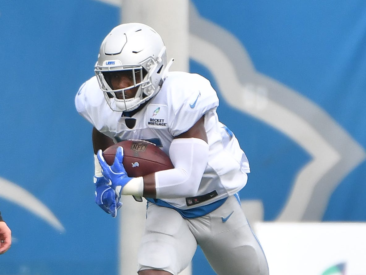 Lions running back Theo Riddick runs through the obstacles during drills.