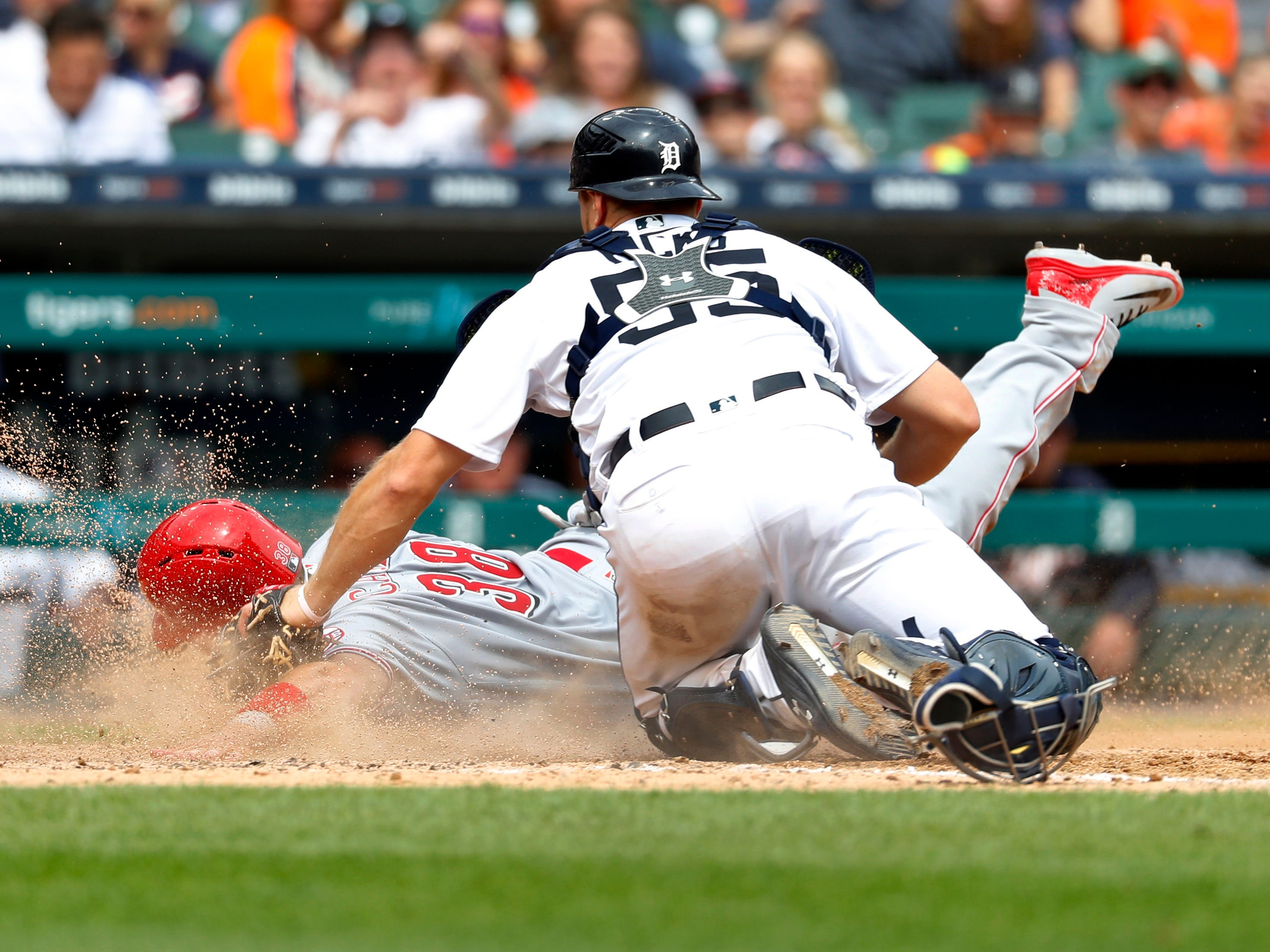 Tigers catcher John Hicks  tags out Cincinnati's Curt Casali at home plate in the seventh inning.