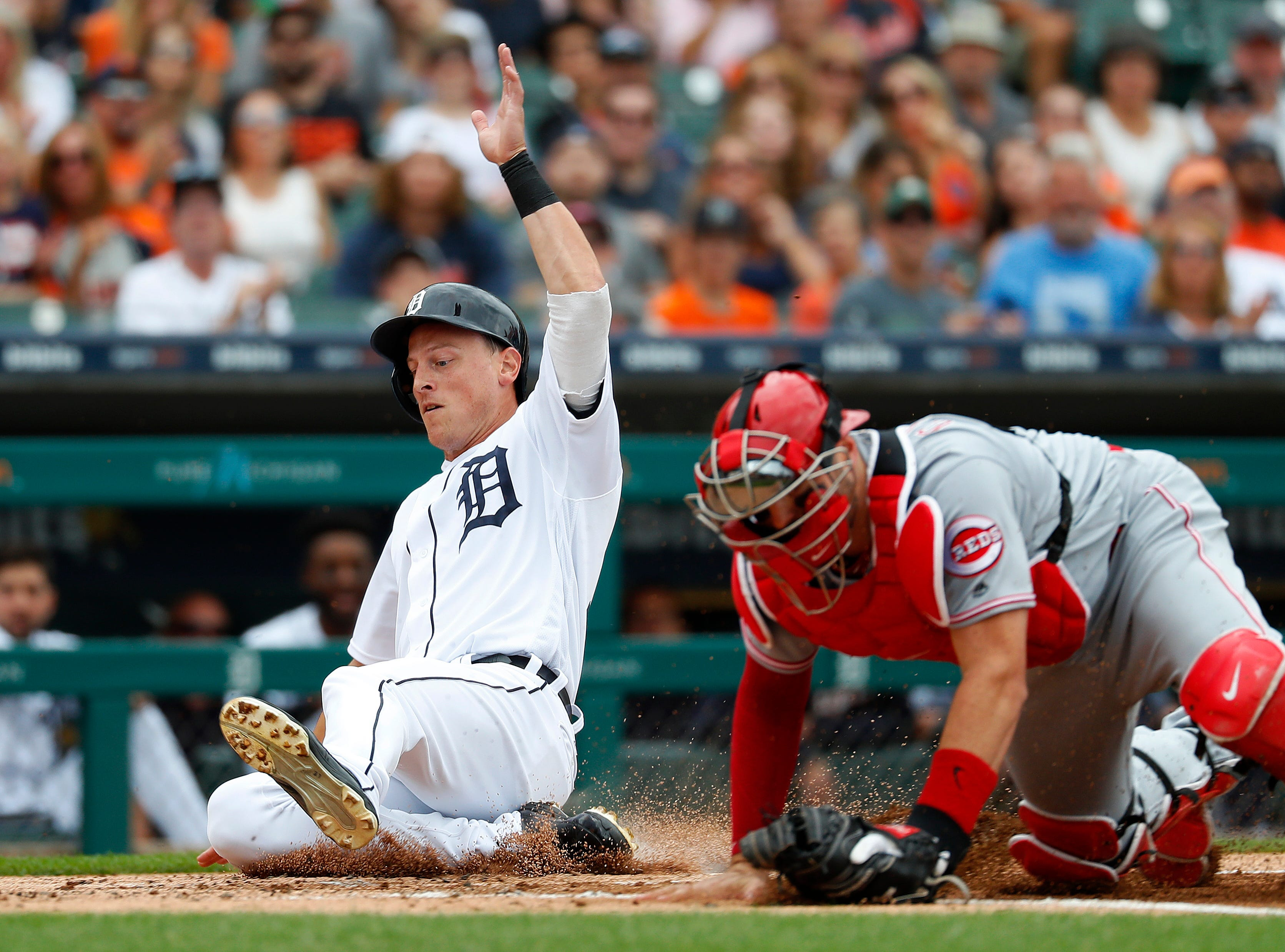 The Detroit Tigers' Jim Adduci slides safely into home plate as Cincinnati Reds catcher Curt Casali reaches for the throw in the second inning in Detroit, Wednesday, Aug. 1, 2018.  The Tigers won, 7-4.