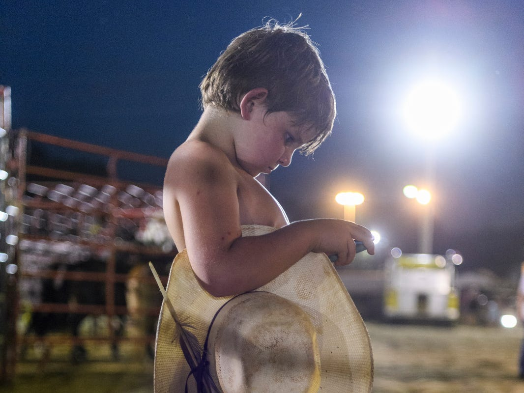 "Wheaton West, 5, of Jasonville, Ind., takes a break from packing up his rodeo gear at the Gibson County Fairgrounds in Princeton, Ind., Tuesday, July 10, 2018. This is West's first year competing in rodeo competitions around the mid-west alongside his brother Warren West, 9, who started bull riding at the same age. ""They are Bronc riding, bull riding son of a guns,"" one of their family members said."
