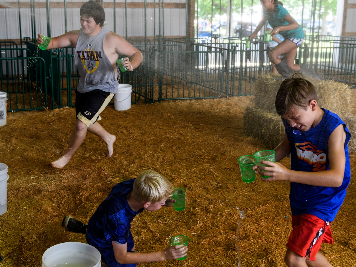 "Volunteer Kathy Klueg, not pictured, soaks 4-Hers as they compete in the straw bale relay during the 4-H Barn Olympics inside the Livestock Barn at the Vanderburgh County Fair, Monday afternoon, July 23. ""We want to have fun with the kids before all the craziness starts [with animal shows and other fair activities],"" Jill Vieira, a local 4-H leader who organized the games, said."