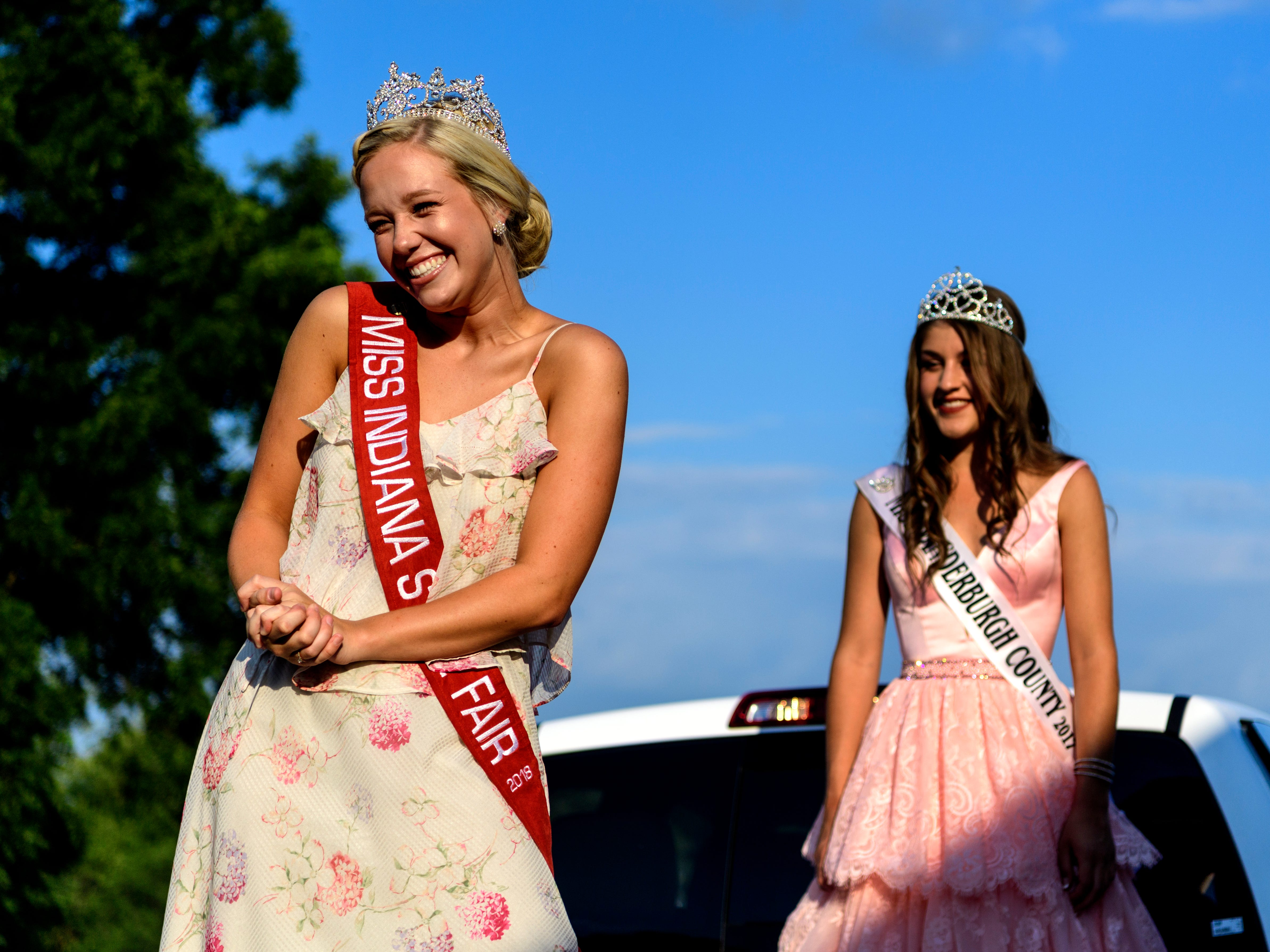 Audrey Campbell, the 2018 Miss Indiana State Fair Queen, left, beams with excitement as she meets fair-goers while riding on the back of a Toyota Tacoma pick-up truck with Holly Witten, the 2017 Miss Vanderburgh County 4-H Fair Queen, right, before attending the Vanderburgh County Fair pageant in the 4-H Center auditorium, Monday evening, July 23, 2018. Campbell, who is the 60th Indiana State Fair Queen, will have traveled to over 40 county fairs around the state by the time fair season is over.