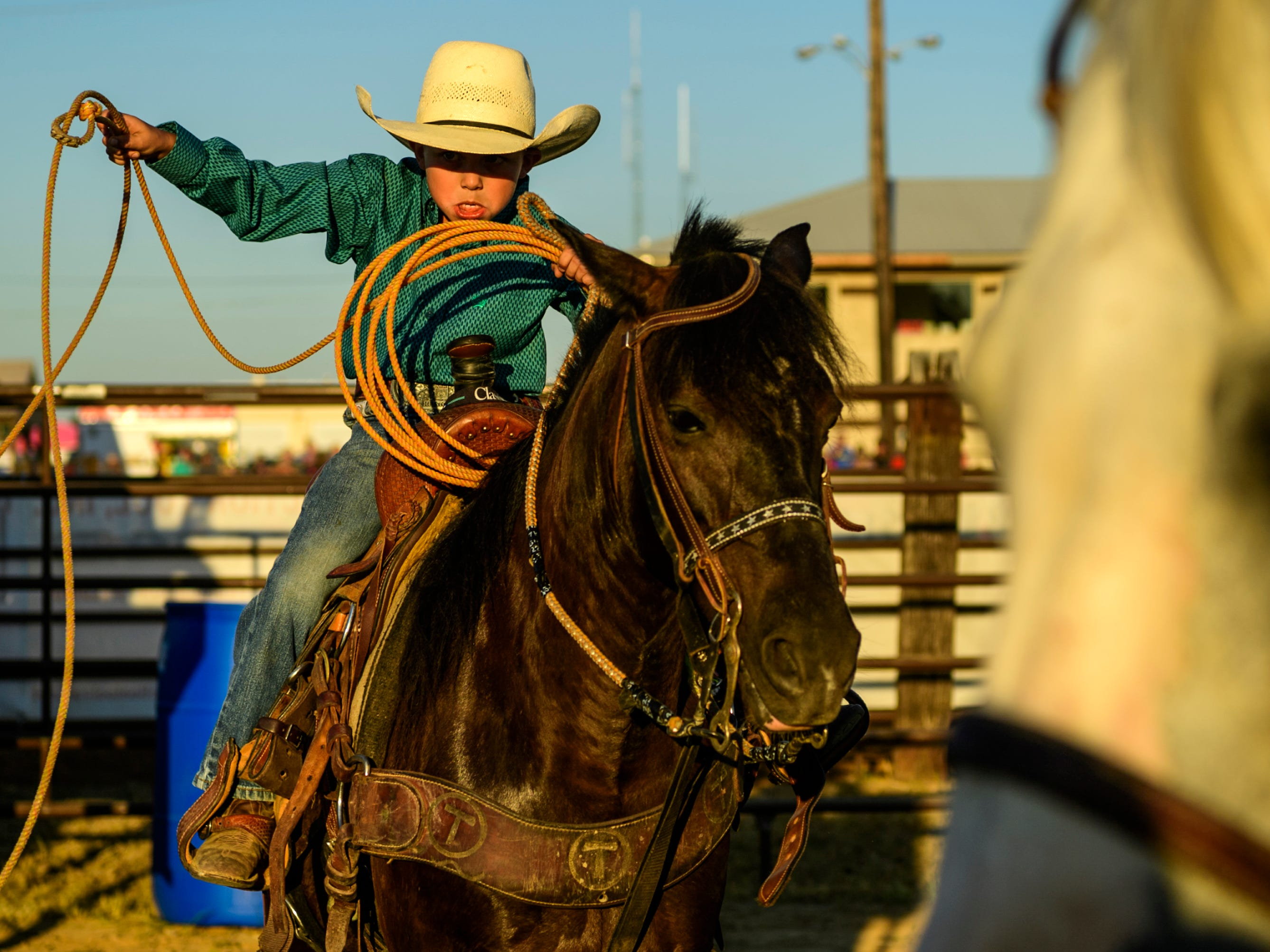 Kayson Wagoner, 6, of Morganfield, Ky., practices roping on his horse Black Magic as they stand beside one of his family's other horses, Speedy, right, during the rodeo show at the Henderson County Fairgrounds, Henderson, Kentucky, Saturday, July 7, 2018.