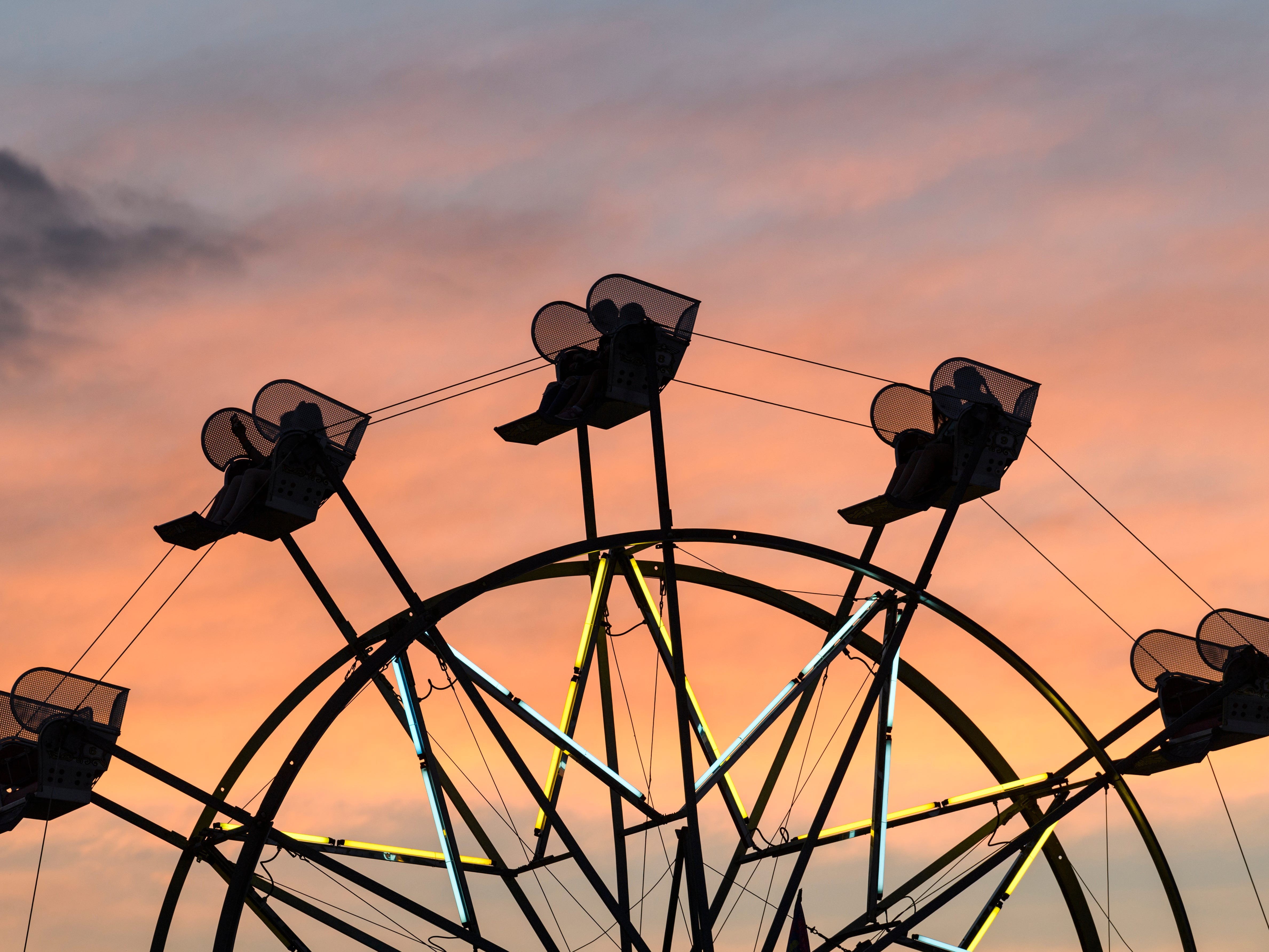 Fair-goers go round-and-round on the Ferris wheel as the sun sets behind them on the last day of the Vanderburgh County Fair in Evansville, Ind., Saturday, July 28, 2018.