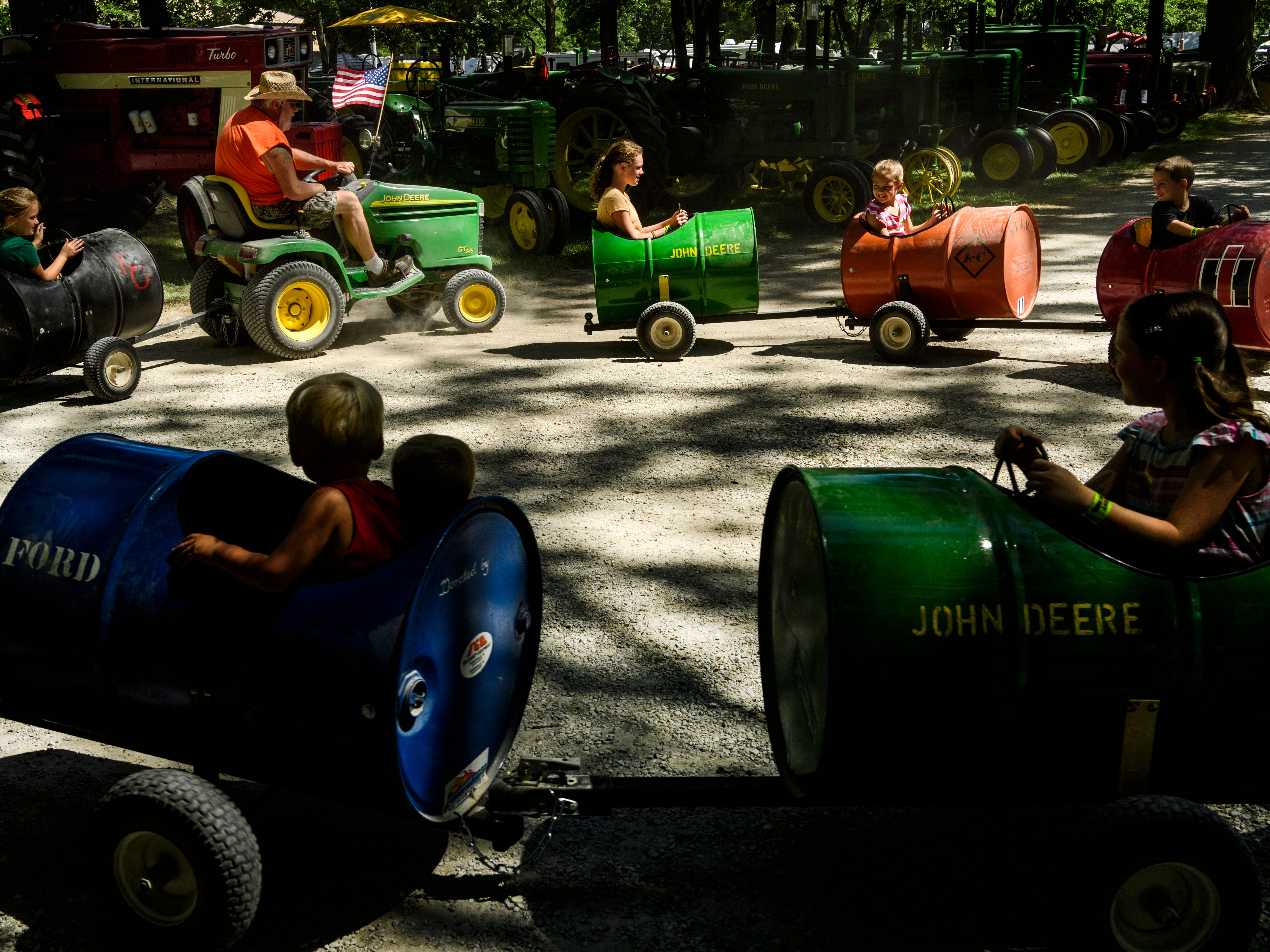 Rick Conner, top left, drives the Southern Indiana Antique Machinery Club's barrel train around a display of over 200 tractors set up for Vanderburgh County Fair-goers on the 4-H Center grounds, Wednesday afternoon, July 25, 2018.