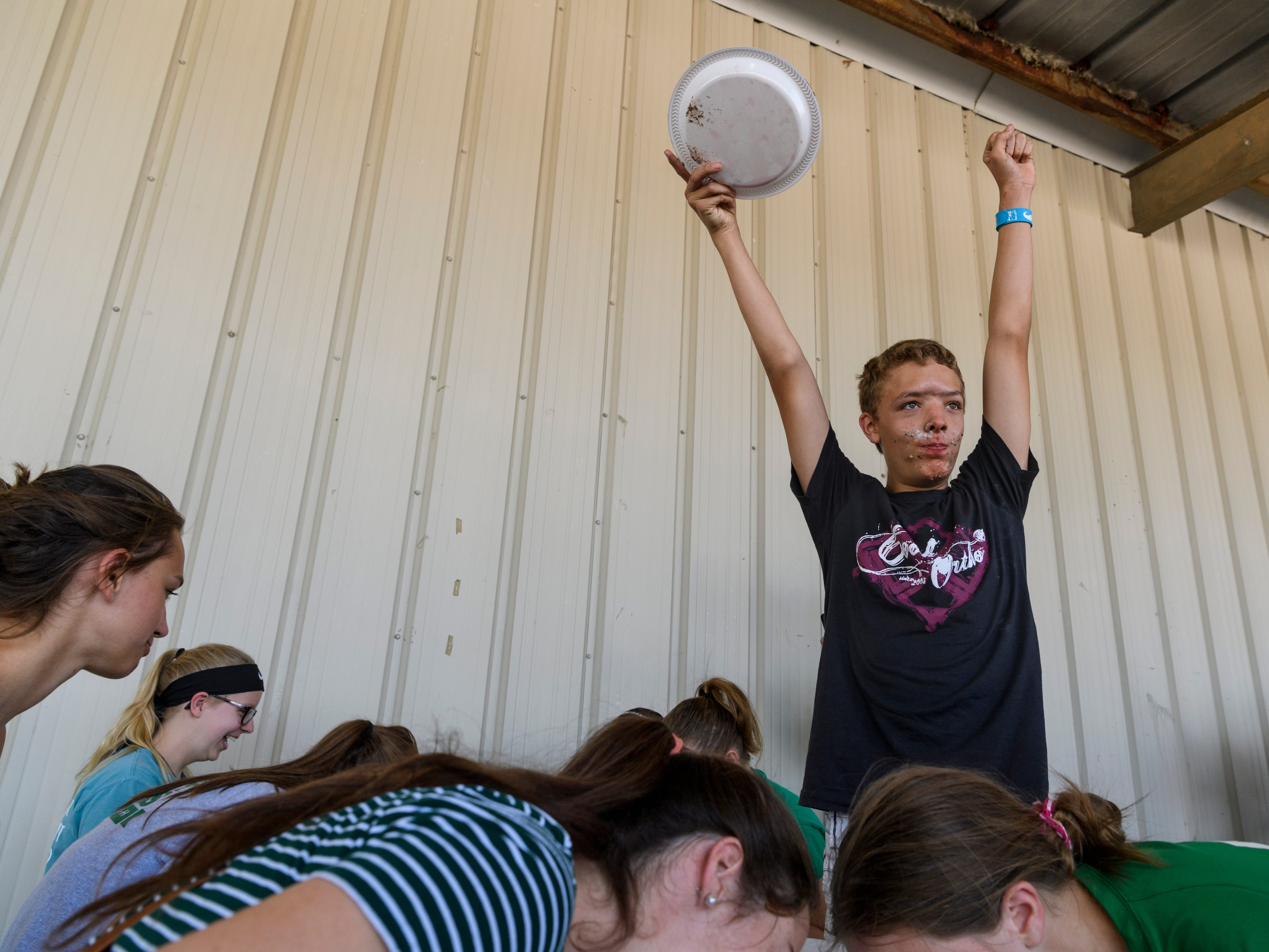Levi Riggs triumphantly raises his arms up after finishing a piece of watermelon during the Vanderburgh County Fair watermelon eating contest held outside the Banquet Hall at the 4-H Center in Evansville, Ind., Thursday afternoon, July 26, 2018. Remnants of pie were seen on his and other contestants faces because they had competed in the pie eating contest right before digging into juicy watermelon slices.