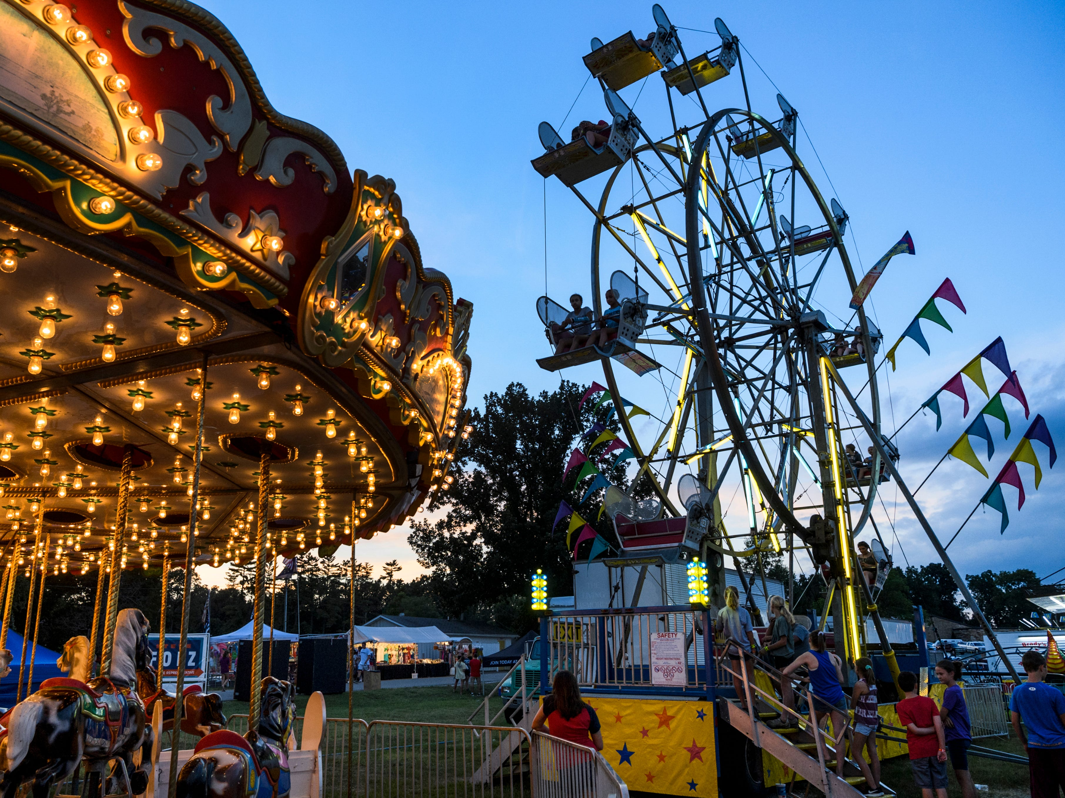 The Merry-Go-Round and Ferris wheel light up the midway during the last night of the 2018 Vanderburgh County Fair, Saturday, July 28, 2018.