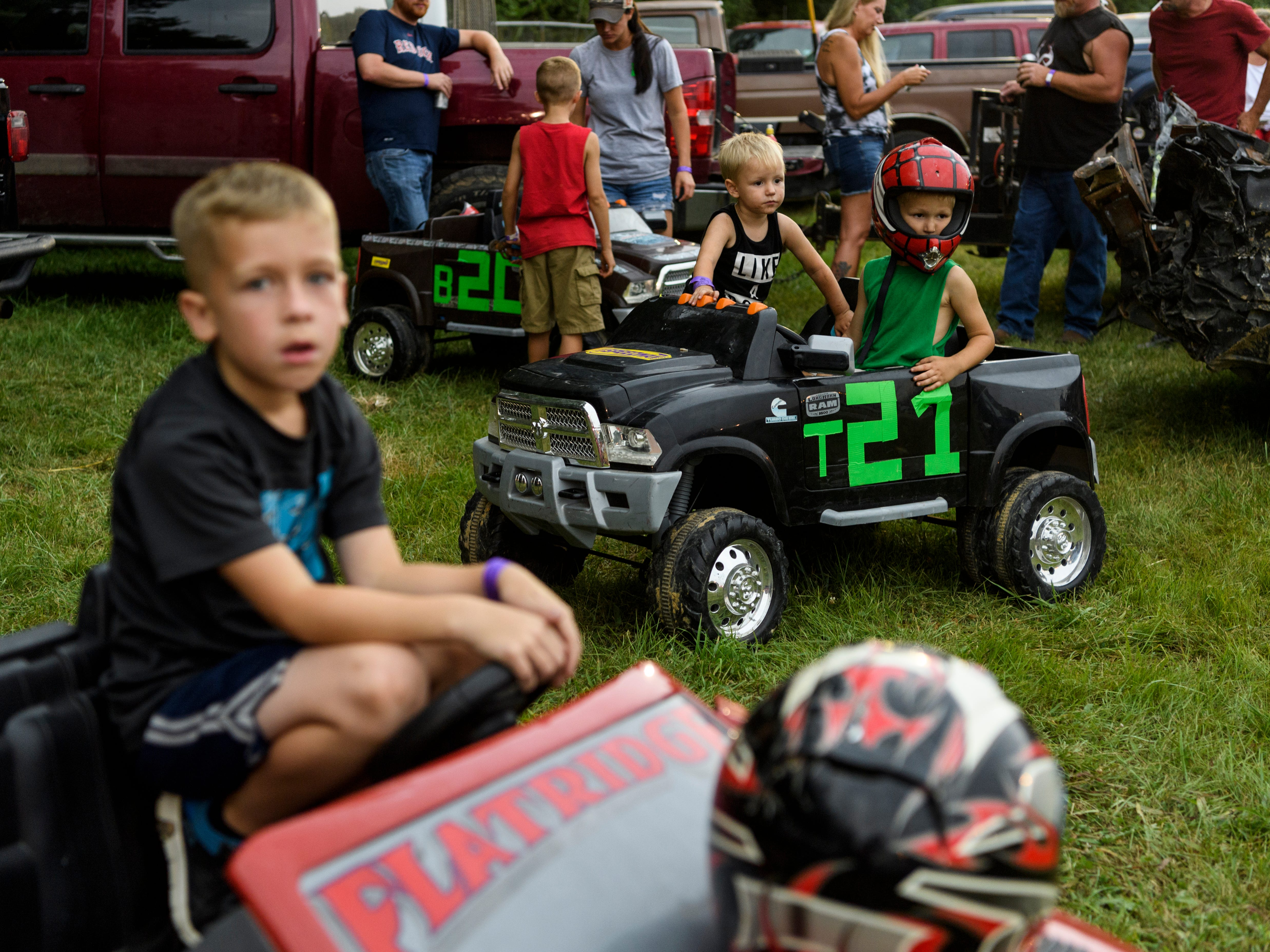 Declan Tooley, 6, from front left, Brigston Baum, 2, and Trace Spurgeon, 5, wait for the lightening and thunder to pass so they can compete in the Gibson County Fair's Powerwheels Demo Derby at the fairgrounds in Princeton, Ind., Saturday, July 14, 2018. The stormy weather cleared up enough for them to compete and be able to watch the demo derby later that night.