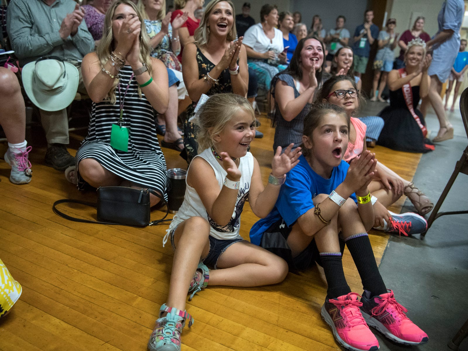 Elsey Lyke, 6, left, Lynn Wade, right, and Olivia Wade, 6, back, and other audience members cheer on their camp counselor Brooke Bittner as she is named Fourth Runner-Up Miss Vanderburgh County during the Vanderburgh County Fair pageant, Monday evening, July 23, 2018.