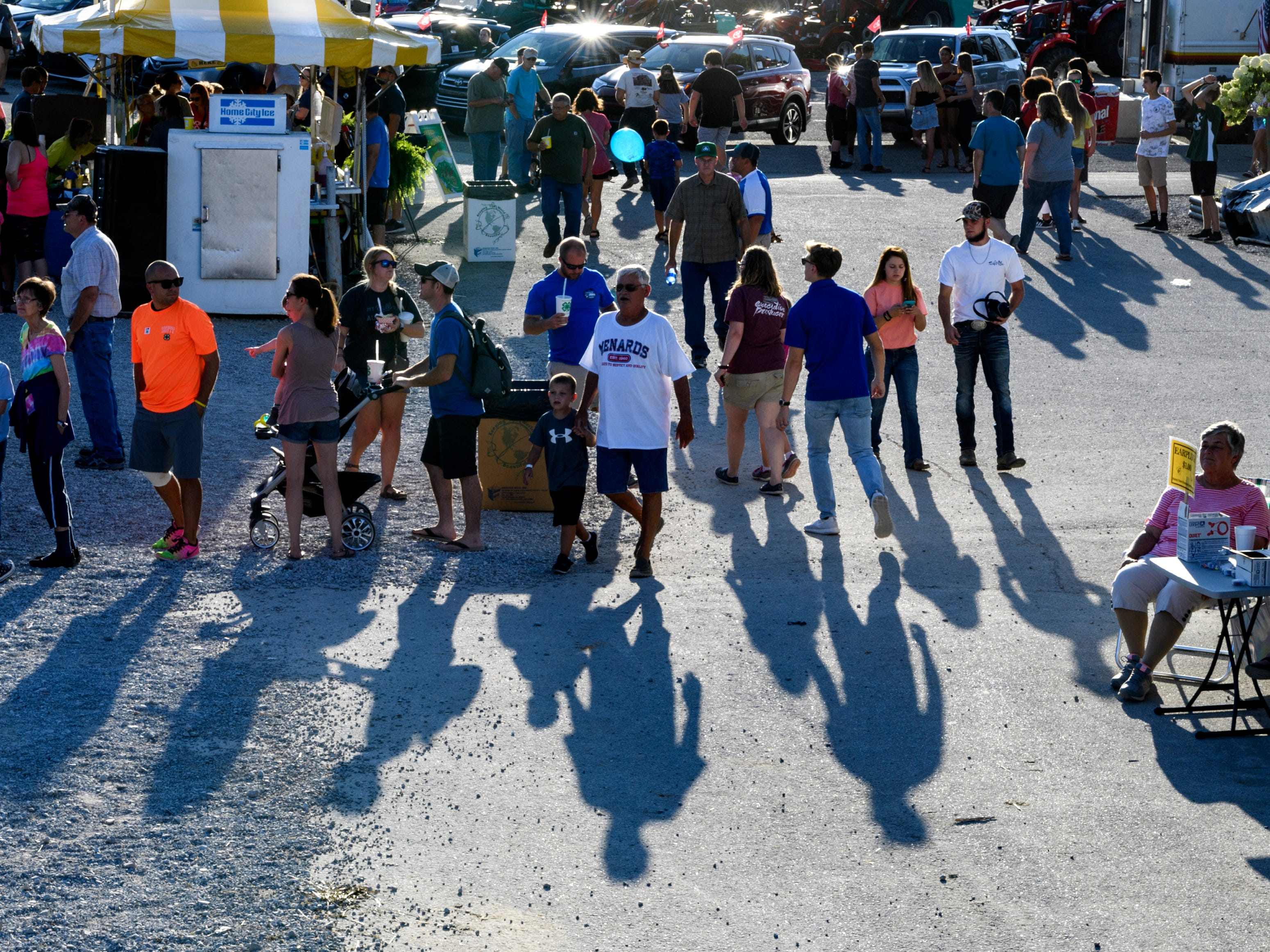 People wait in line for food from the Junior Leader and Young Dairyman Food Booths that are set up beside the grandstands during the Vanderburgh County Fair, Friday evening, July 27, 2018.