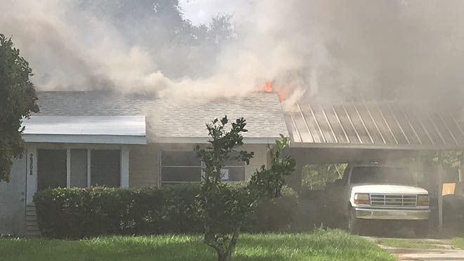 Flames shoot from the roof of a home in the 2300 block of Unity Avenue in Fort Myers on Wednesday morning. The home's occupant was not home at the time of the fire.