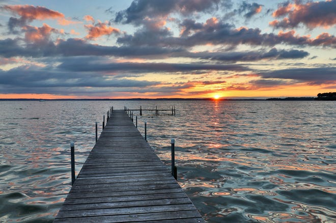 Landscape with wooden pier and dramatic summer sunset over the lake Mendota, city of Madison, Wisconsin, Midwest USA.