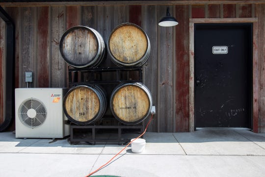 Barrels are stacked up outside of Rapid Creek Cidery on Wednesday, Aug. 1, 2018, in Iowa City, Iowa. The lower floor of the building is designed for events and has a chapel area for weddings down a brick walkway.