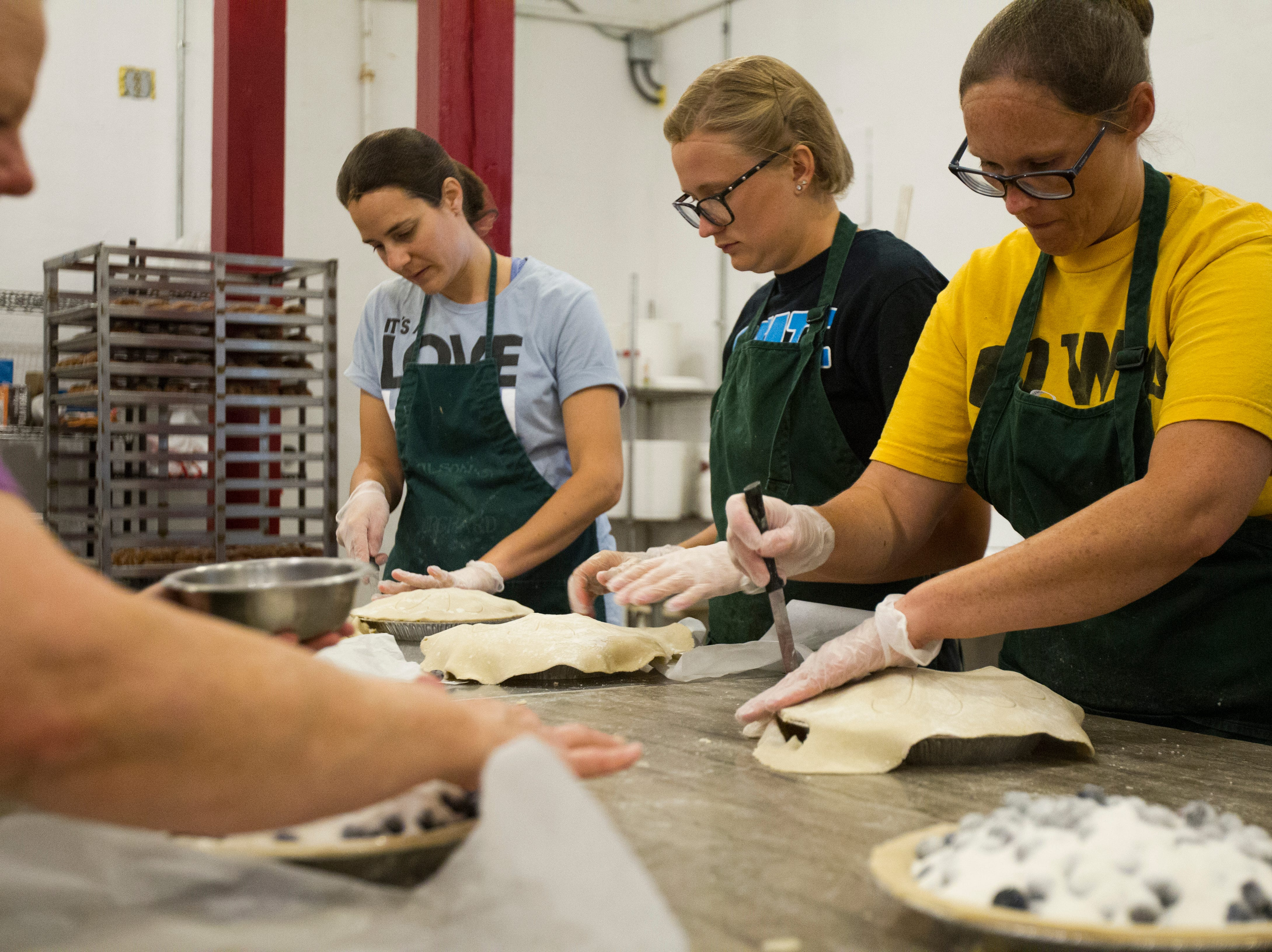 Members of the Wilson's bakery crew make blueberry pies on Wednesday, Aug. 1, 2018, at Wilson's Apple Orchard in Iowa City, Iowa. The orchard is open from Aug. 1 through Oct. 31, 10 a.m. to 6 p.m daily.