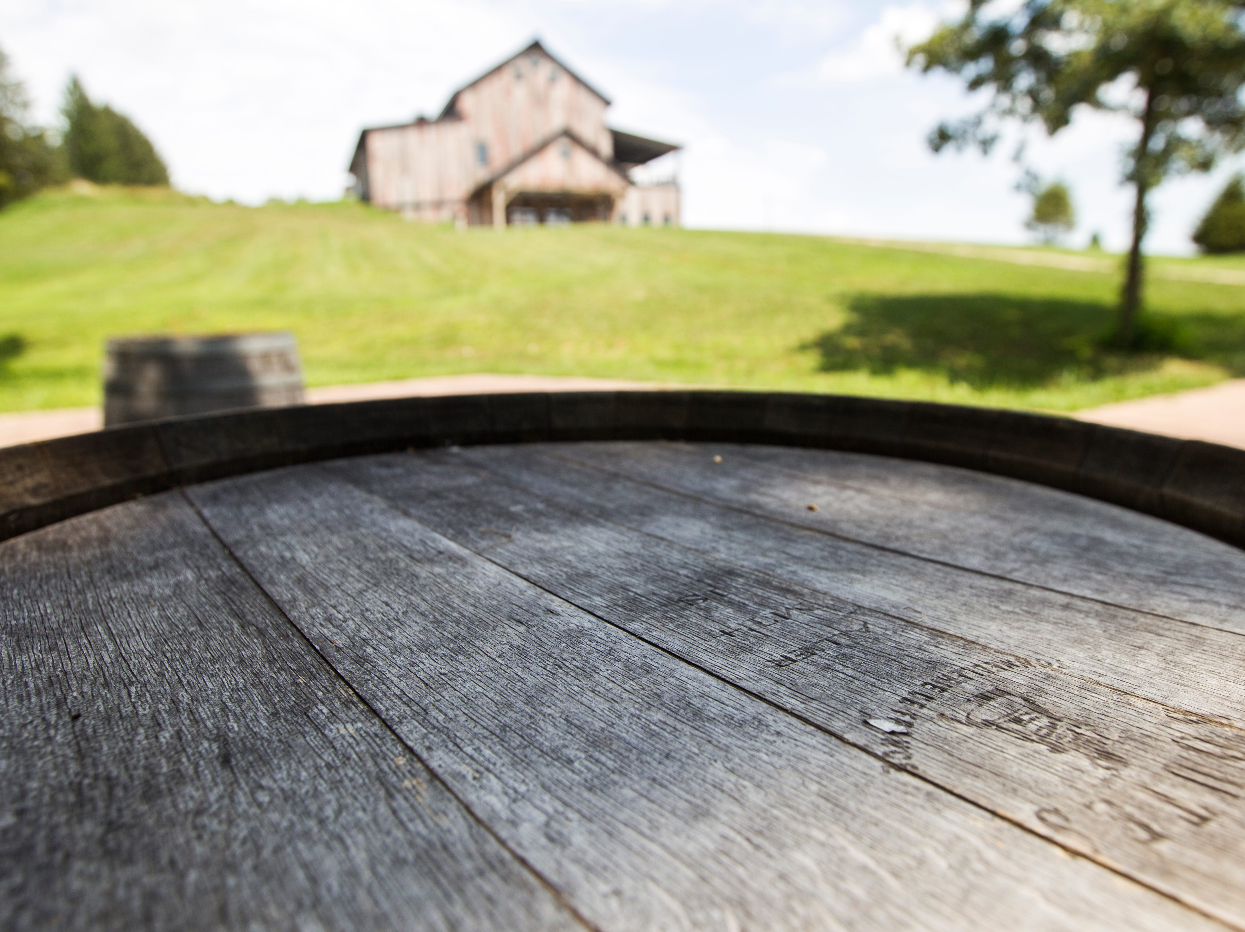 A barrel behind Rapid Creek Cidery is seen on Wednesday, Aug. 1, 2018, in Iowa City, Iowa. The lower floor of the building is designed for events and has a chapel area for weddings down a brick walkway.
