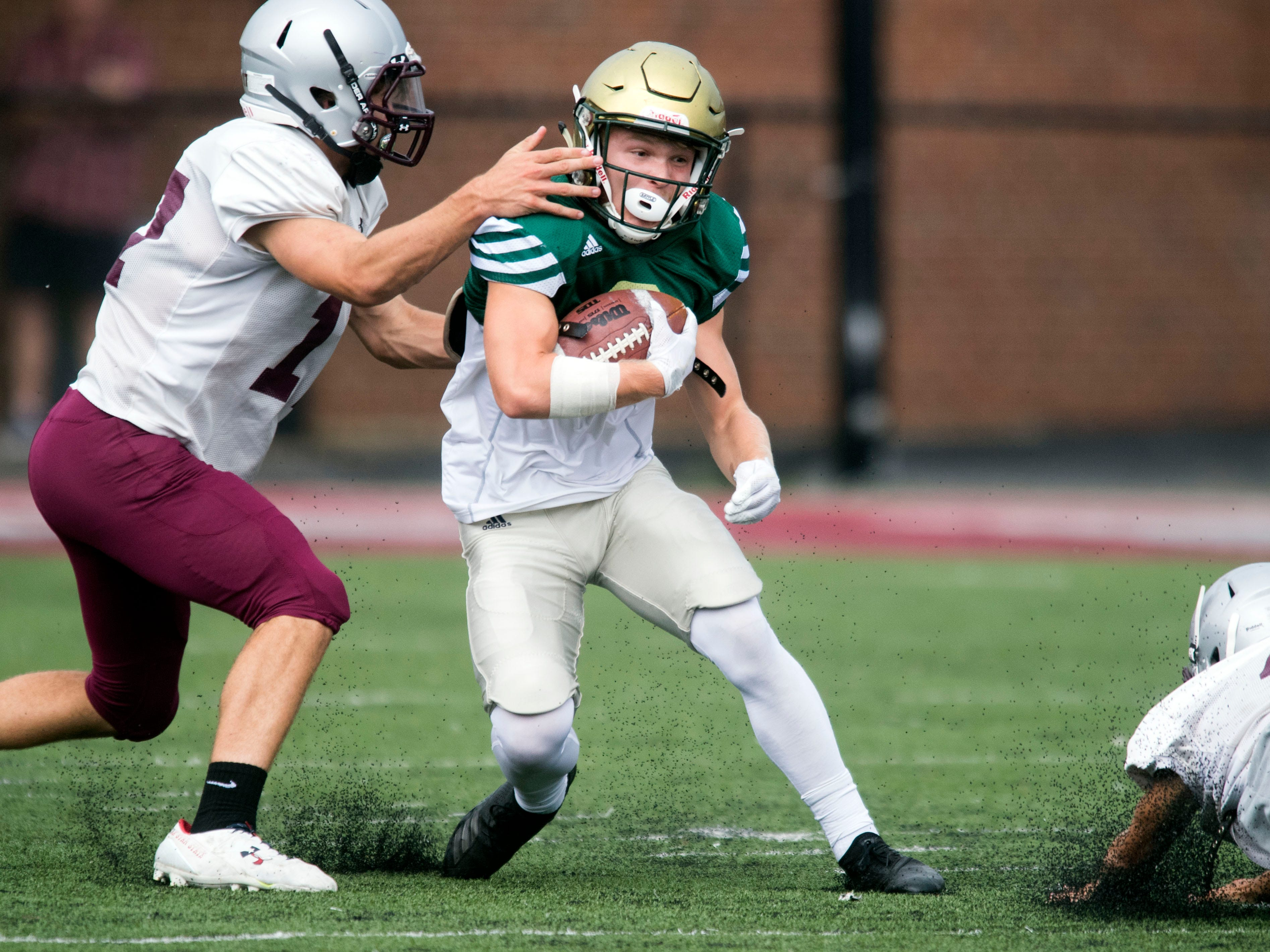 Catholic's Taylor Shannon (2) is grabbed by Alcoa's Adam Mathews (17) during a football scrimmage on Tuesday, July 31, 2018.