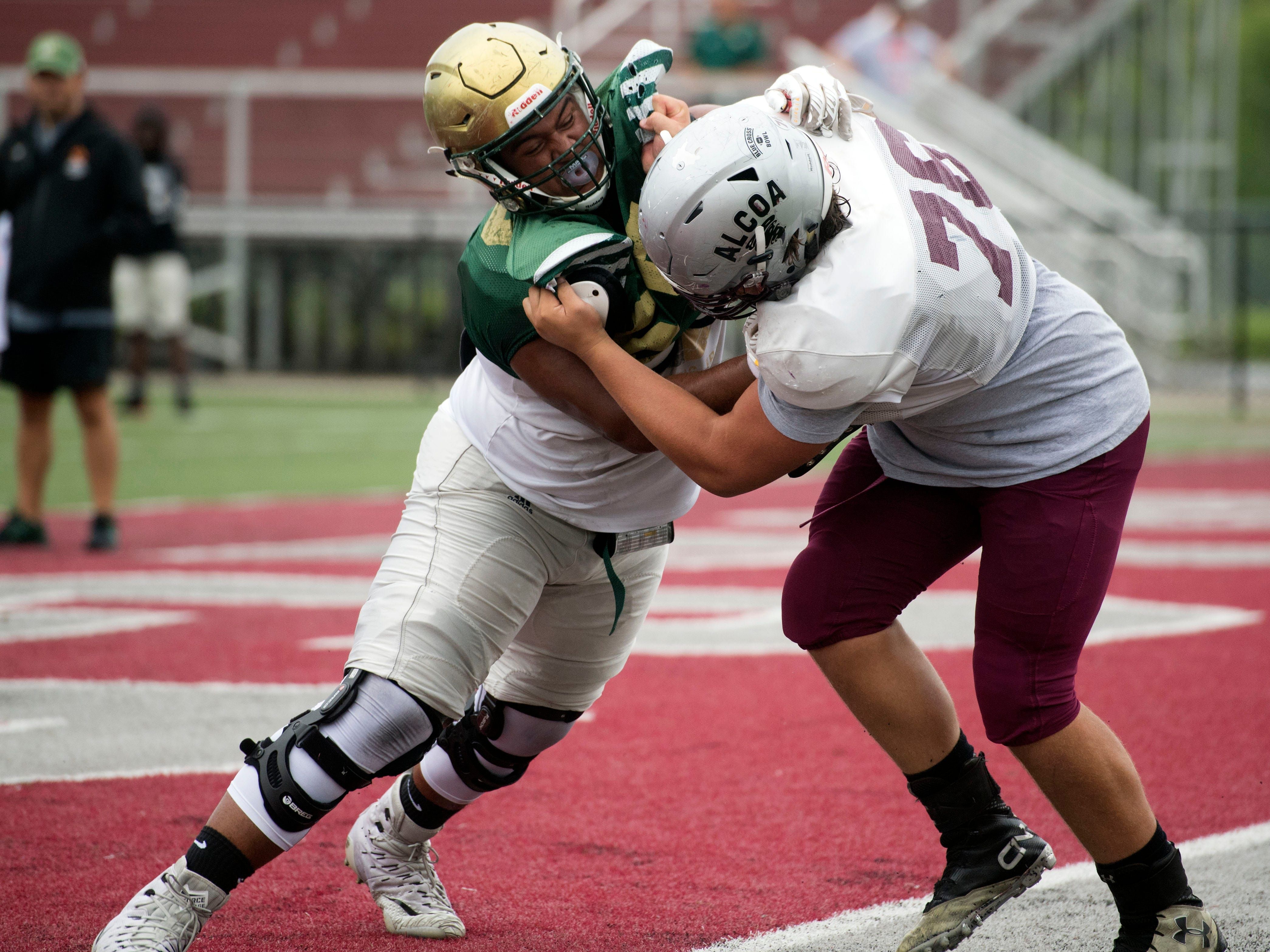 Knoxville Catholic's Bryn Tucker (55) and Alcoa's Brackston Alford (76) run drills before the start of their football scrimmage on Tuesday, July 31, 2018.