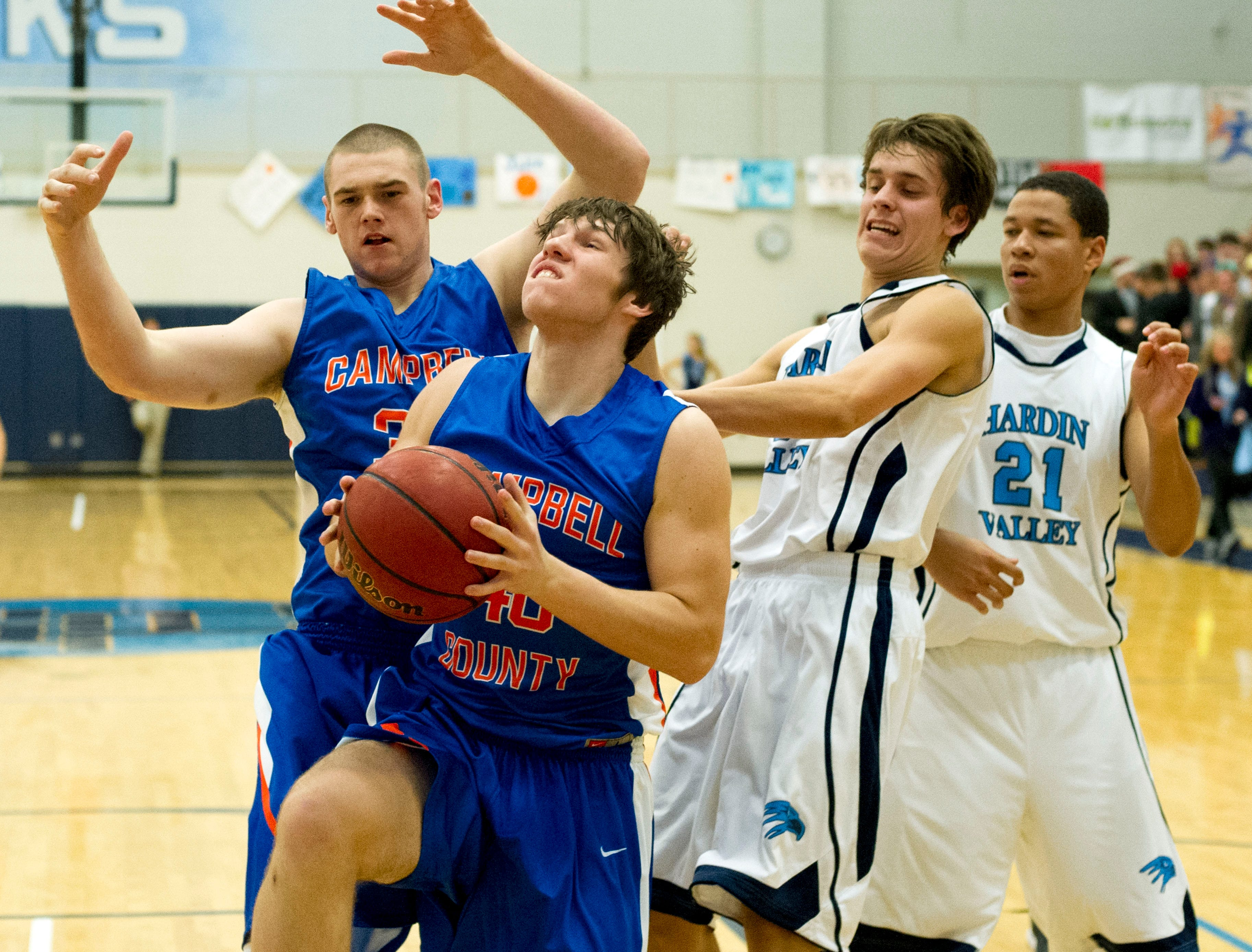 Campbell County's Rosnor Letner looks to the basket while supported by teammate Gunner St. John and defended by Hardin Valley's Daniel Linebaugh, left, and Jalen Carter at Hardin Valley Academy on Thursday, December 13, 2012.
