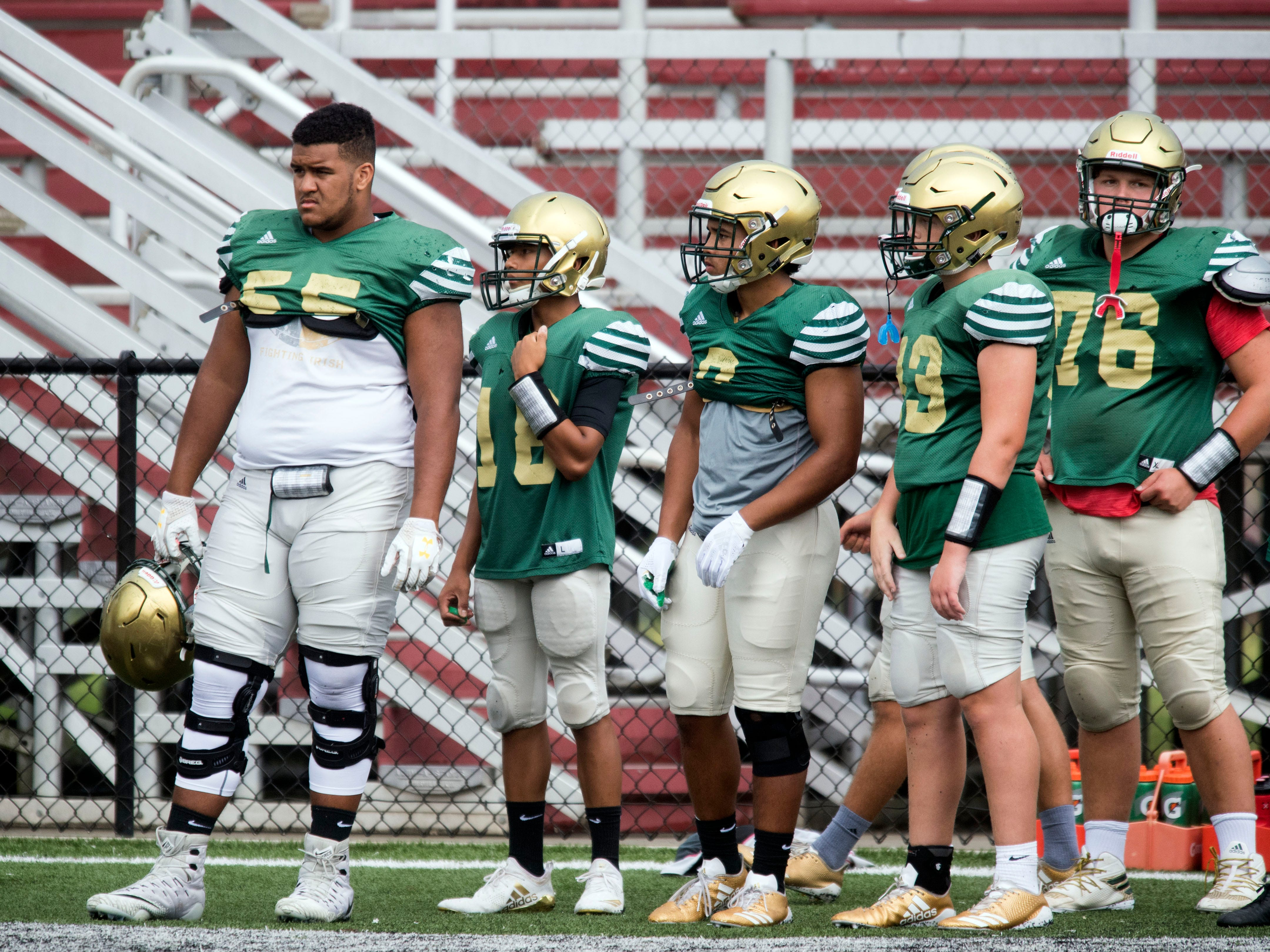 Catholic's Bryn Tucker (55), left, with teammates at Alcoa during a football scrimmage on Tuesday, July 31, 2018.