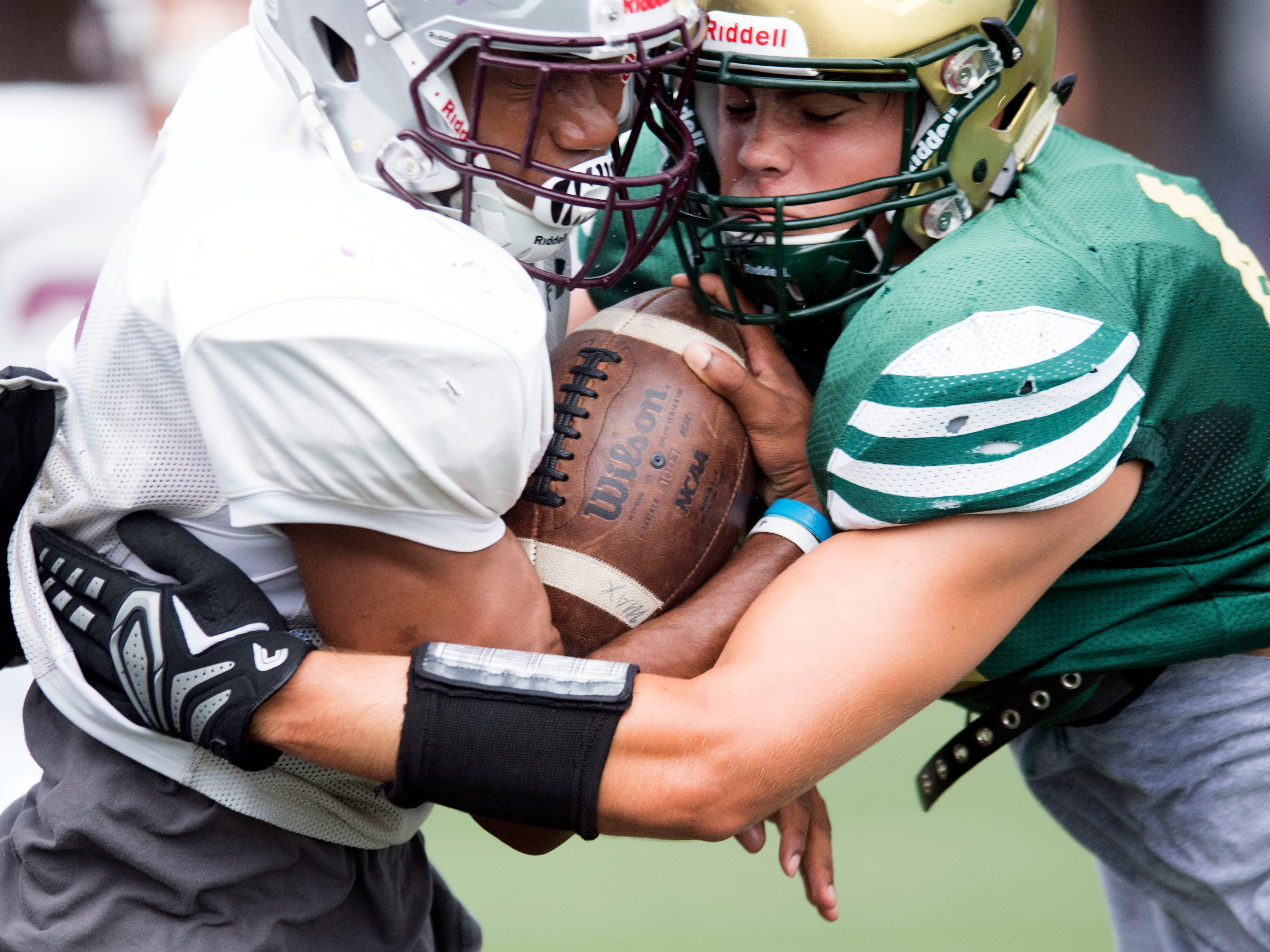 Alcoa's Kareem Rodriguez (6) comes up against Catholic's Connor Cress (48) during a football scrimmage on Tuesday, July 31, 2018.