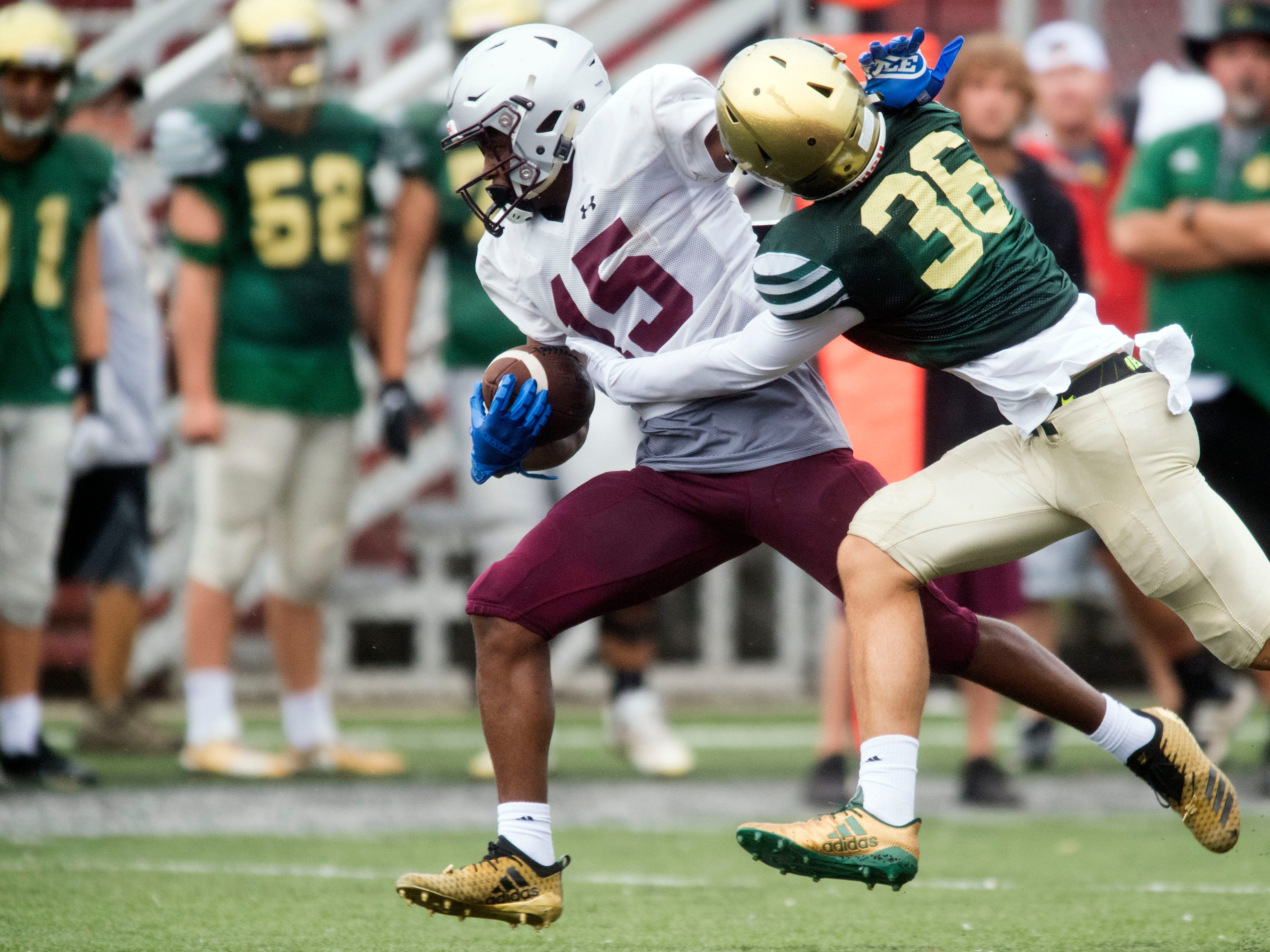 Alcoa's Ahmauud Sankey (15) is grabbed by Knoxville Catholic's Zachary Shannon (36) during a football scrimmage on Tuesday, July 31, 2018.