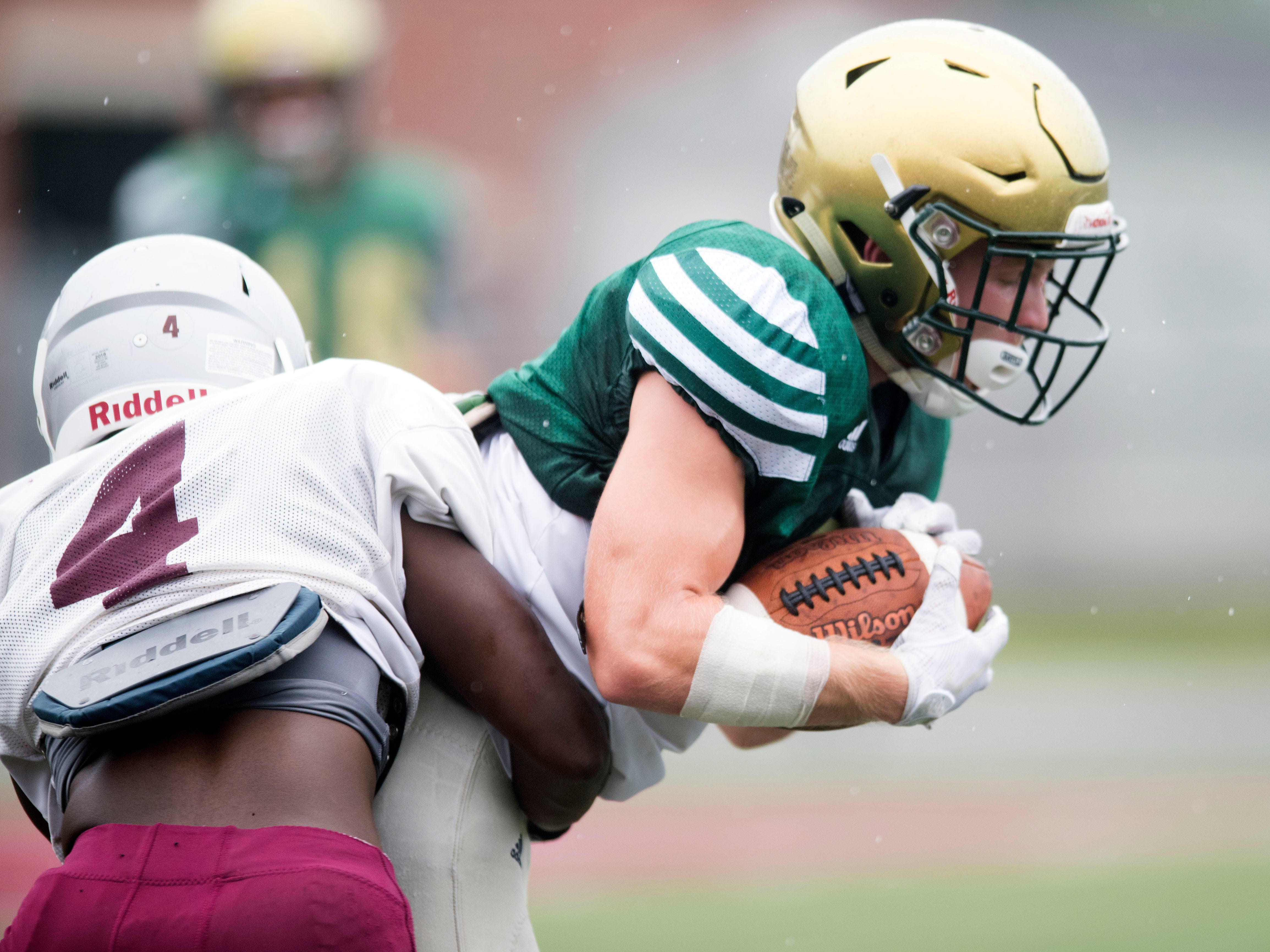 Knoxville Catholic's Taylor Shannon (2) makes a catch just as he is tacked by  Alcoa's Makel Petty (4) during a football scrimmage on Tuesday, July 31, 2018.