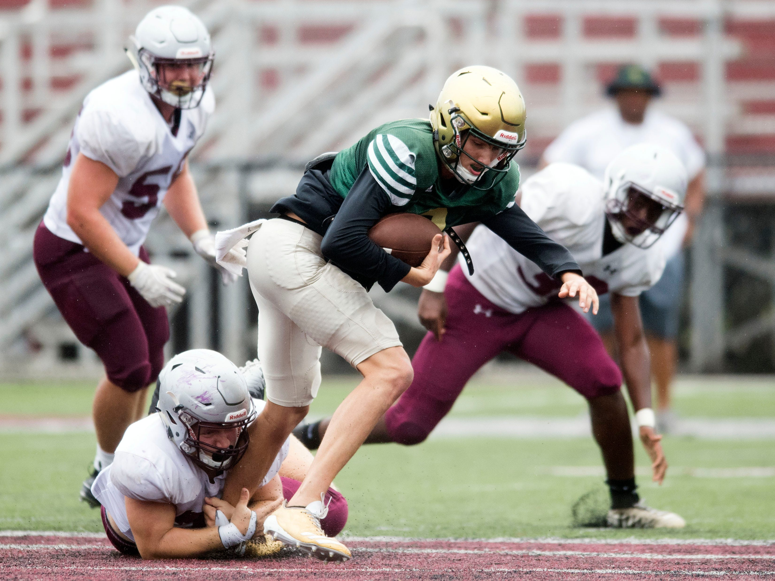 Knoxville Catholic's Jack Jancek (3) is grabbed by Alcoa's Malachi Jared (35) during a football scrimmage on Tuesday, July 31, 2018.