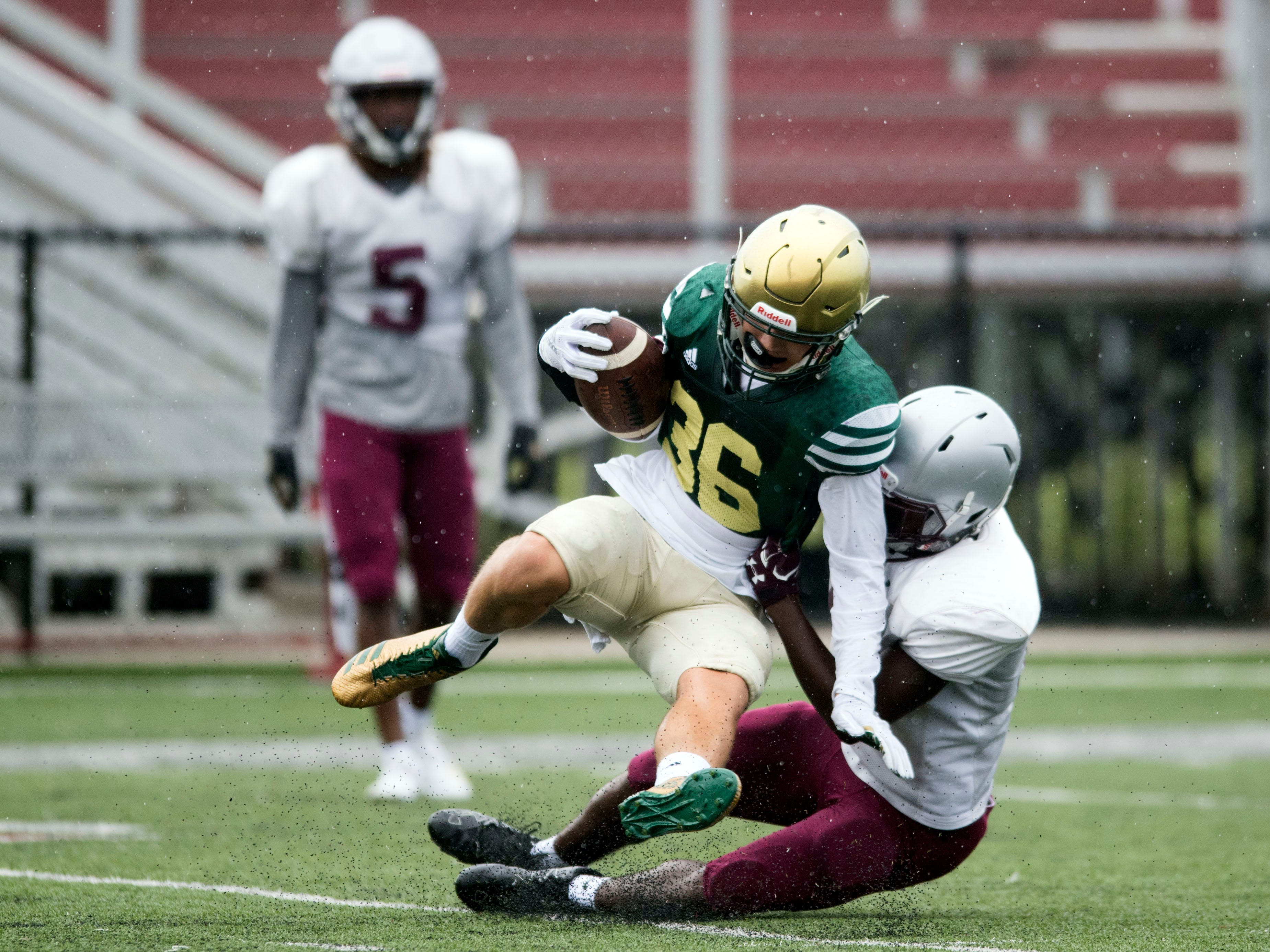 Knoxville Catholic's Zachary Shannon (36) is tackled by Alcoa's Isaiah Bryant (16) during a football scrimmage on Tuesday, July 31, 2018.