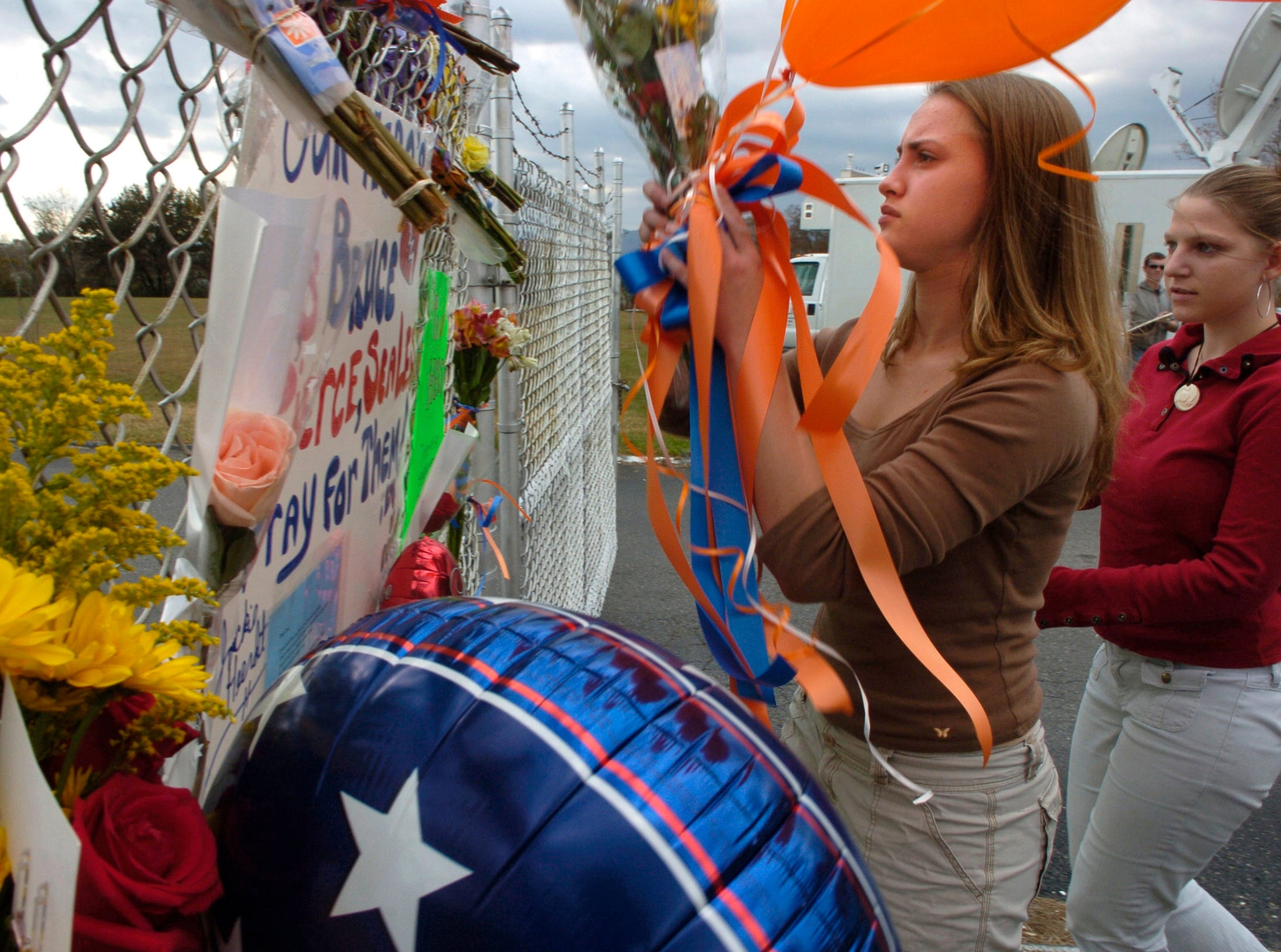 Freshman Megan Ford,14, left,   and sophomore Jane Haun, 15, place flowers and balloons on a makeshift memorial for three shooting victims  Tuesday  at Campbell County High School November 8, 2005.  Student  Kenneth S. Bartley, 14, is  accused of killing assistant Ken Bruce  and seriously wounding two other administrators after they confronted him about having a gun at school.