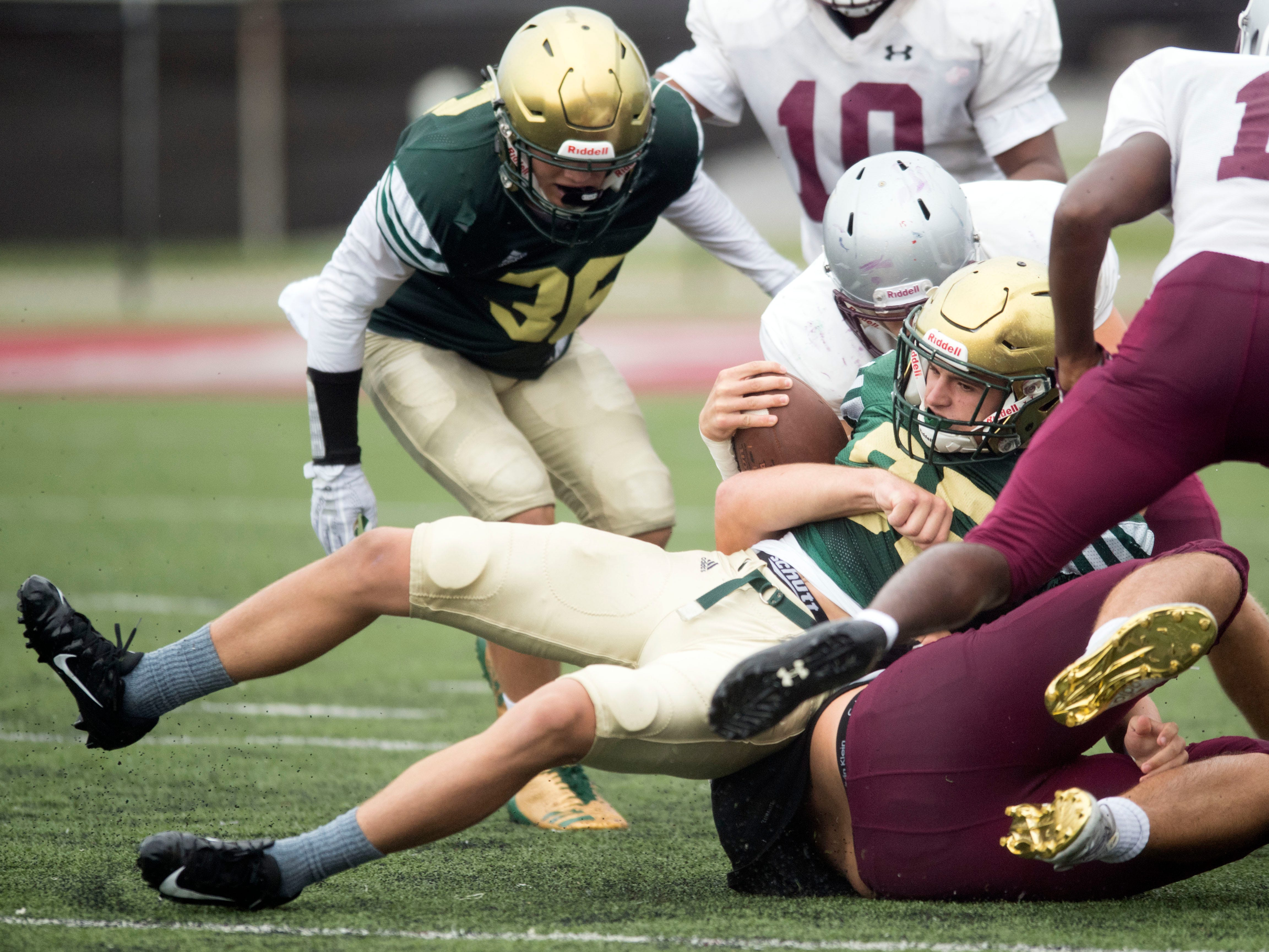Knoxville Catholic's Nicklaus Iverson (35) is tackled during the football scrimmage against on Tuesday, July 31, 2018.