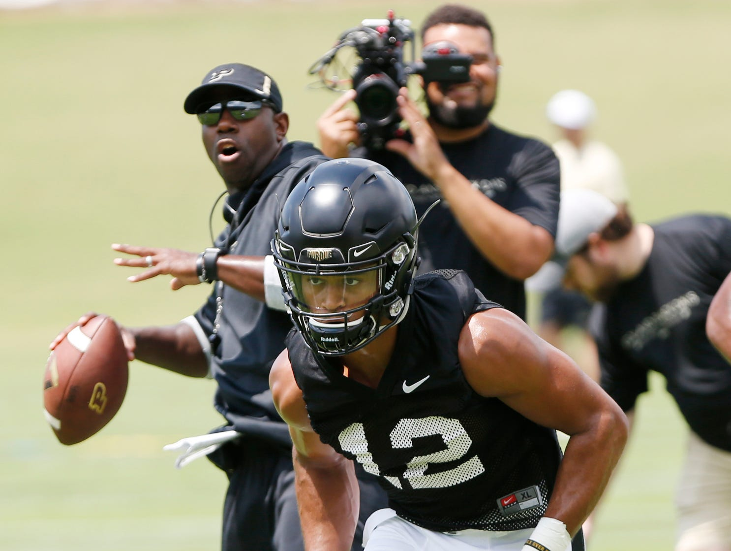 Wide receiver Jared Sparks runs a route as wide receivers coach and co-offensive coordinator Jamarcus Shephard (background) prepares to through the pass during football practice Wednesday, August 1, 2018, at Purdue.