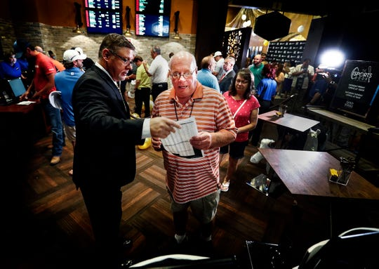 Gold Strike Casino employee Robert Leise has over a sports betting sheet to Bill Beil (middle) of Columbia, Tn., during the grand opening celebration of sports betting in Tunica. Mississippi is the third state to offer legalized sports betting since the Supreme Court ruling allowing states to offer sports wagers.
