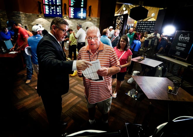 Gold Strike Casino employee Robert Leise hands over a sports betting sheet to Bill Beil of Columbia, Tenn., during the grand opening celebration of sports betting in Tunica. Mississippi is the third state to offer legalized sports betting since the Supreme Court ruling allowing states to offer sports wagers.