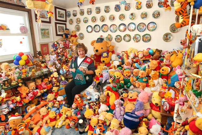 This 2009 photo shows Deb Hoffmann sitting with her large Winnie the Pooh collection inside her town of Vernon home. Hoffmann is holding a copy of the 2010 Guinness World Records book where her collection is featured.