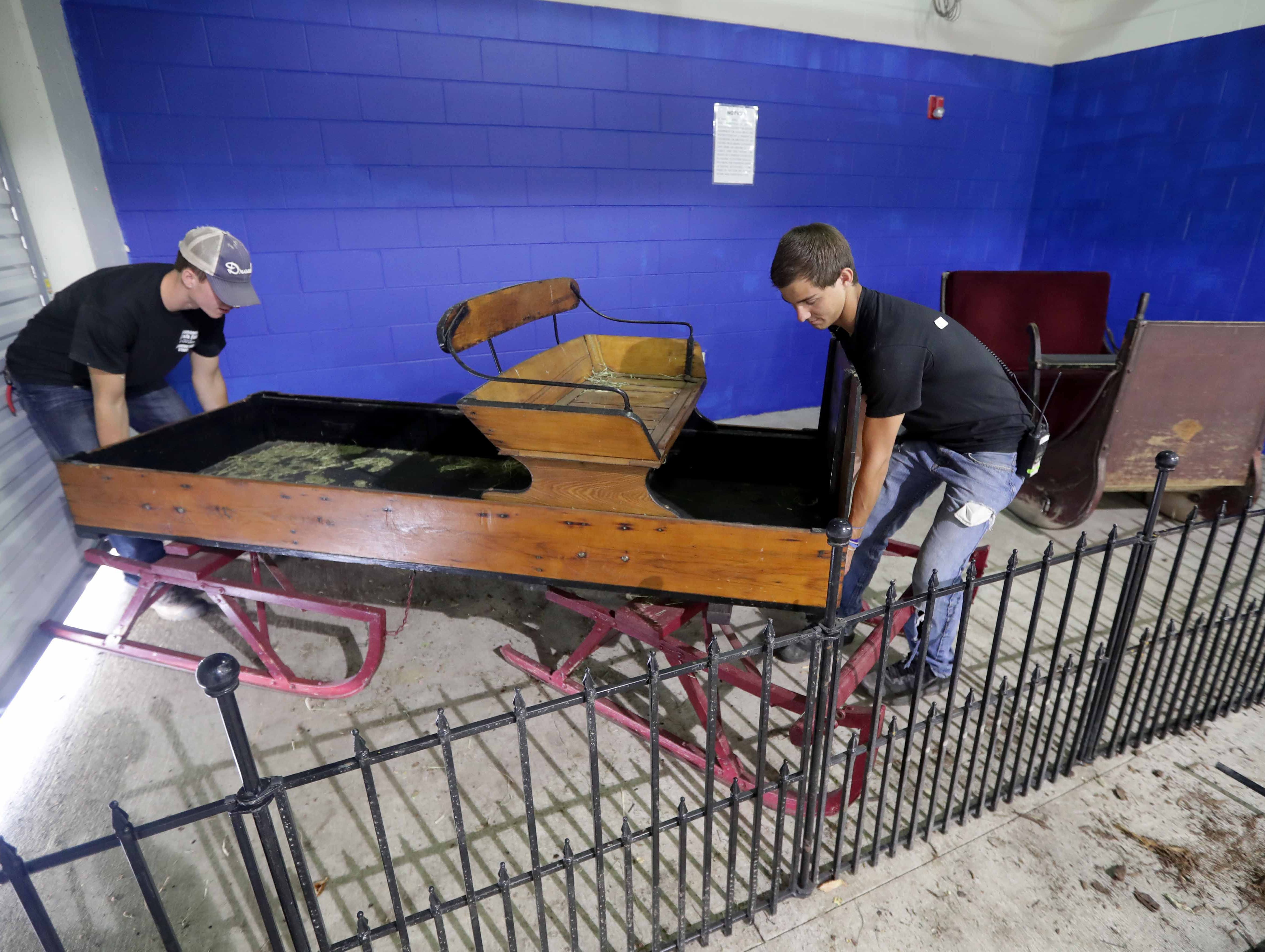 Collin Sauer (left) and Rylie Waeffler, both Wisconsin State Fair agriculture assistants, work on moving an antique sleigh that was at one time pulled by horses inside the newly expanded Neighborhood Corral where horses are exhibited. Work was being done in preparation for the opening of the Wisconsin State Fair at State Fair Park on Wednesday, August 1, 2018. The fair, in West Allis, runs from Thursday, August 2 to Sunday, August 12. -  Photo by Mike De Sisti / Milwaukee Journal Sentinel