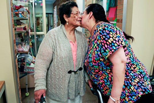 Gloria Romero (left) says goodbye to her daughter, Soraya Cazco, before leaving for a field trip with other seniors at the United Community Center. Cazco is an administrative assistant at the adult day center. Romero has a mild form of cognitive impairment. She has been living with Cazco and her extended family for several years.