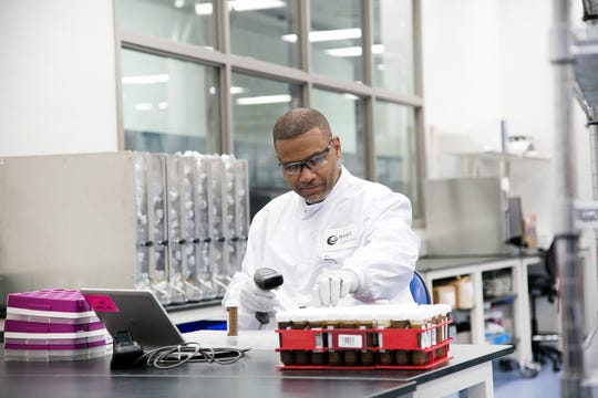 Thad Branch, specimen processing associate, inspects a sample at the Exact Sciences Corp. lab in Madison