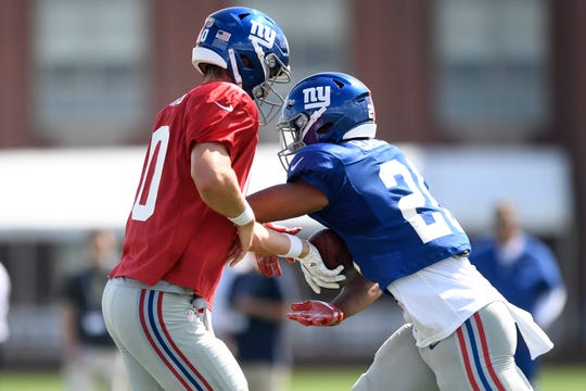 New York Giants quarterback Eli Manning, left, hands the ball off to runningback Saquon Barkley, right, during NFL training camp in East Rutherford, NJ on Wednesday, August 1, 2018.