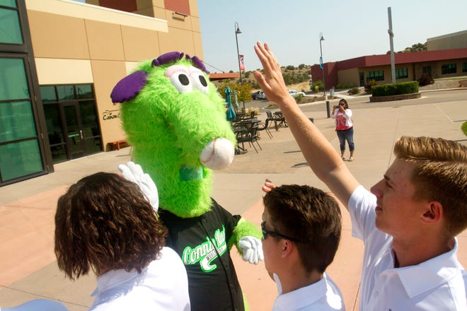 Mack, the Connie Mack World Series mascot, gives high fives to members of the Farmington Fuel Wednesday as they arrive at the Pinon Hills Community Church in Farmington for registration.