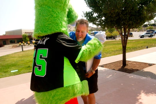 Farmington Fuel Coach Kim Carpenter is greeted by the mascot Mack Wednesday during Connie Mack World Series registration at the Pinon Hills Community Church in Farmington.