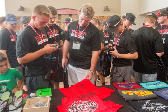 The Nashville Knights' Kaden Dreier, center, looks over merchandise with his teammates Wednesday during Connie Mack World Series registration at the Pinon Hills Community Church in Farmington.