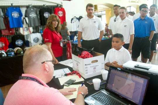 Farmington Fuel bat boy Myles Kee, right, waits for his arrival packet with the rest of his team Wednesday during Connie Mack World Series registration at the Pinon Hills Community Church in Farmington.
