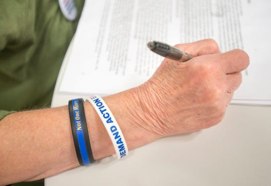 "Betsy Dale Adams, of Gulf Breeze, wears ""Not One More"" and Demanding Action"" bracelets as she talks Wednesday about attending an upcoming Gun Sense University training."