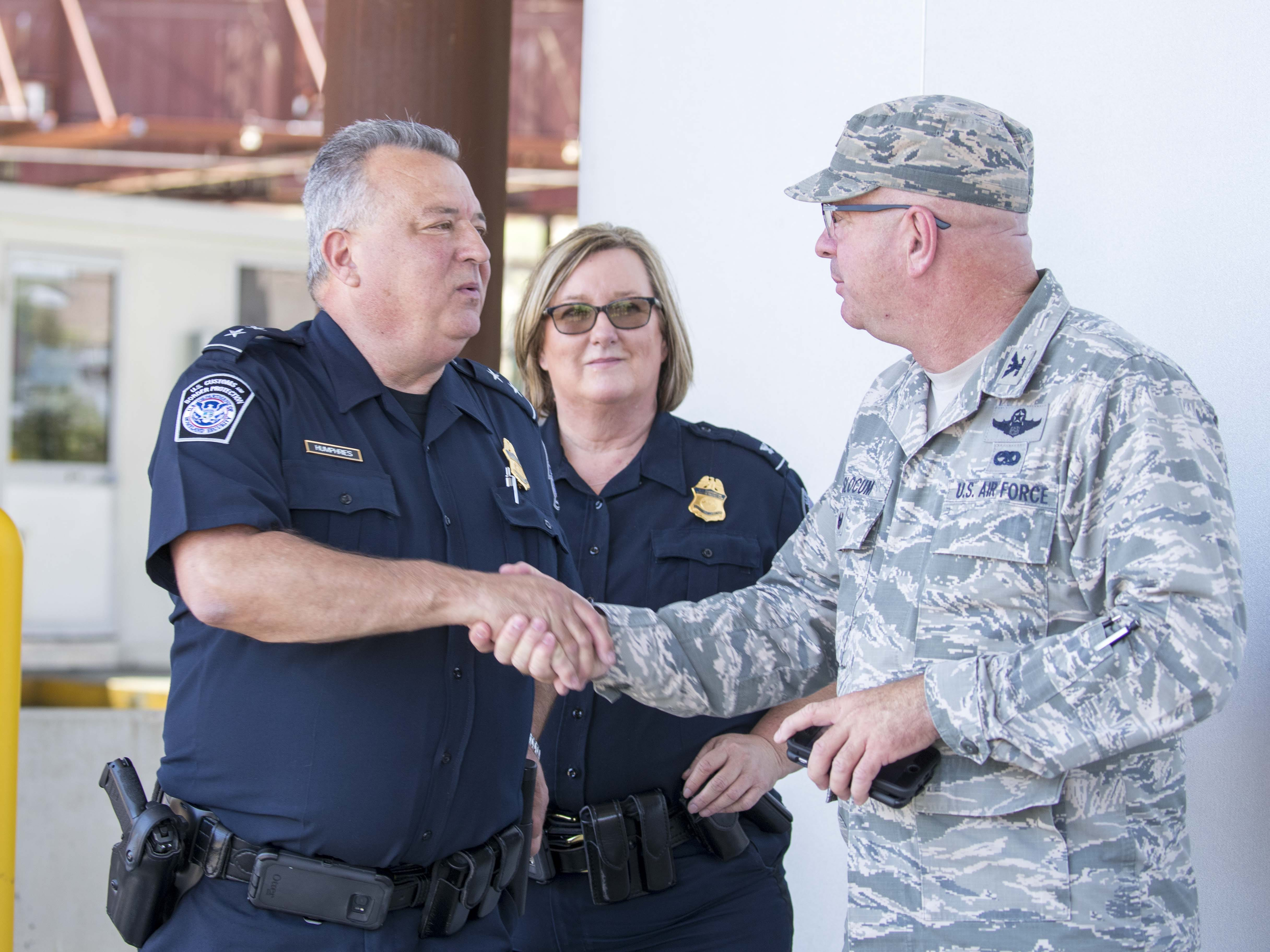 Area Port Director Michael Humphries (left) and National Guard Col. E. Hoyt Slocum, shake hands as personnel perform their Operation Guardian Support responsibilities Aug. 1, 2018, at the Port of Nogales (Mariposa Crossing) in Nogales, Arizona.