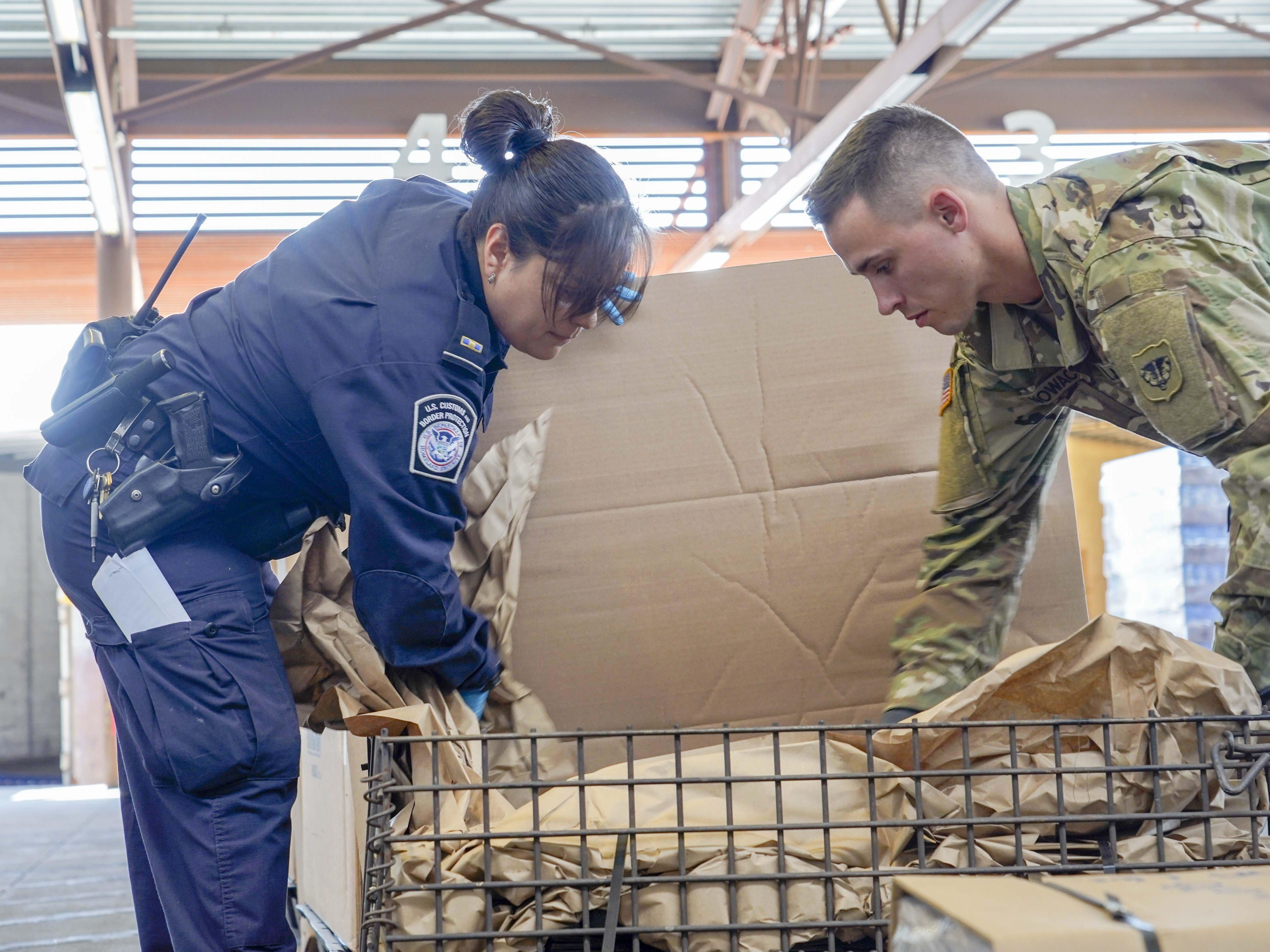 Customs and Border Protection Officer Vanessa Brower and National Guard Spc. Nowack Bradley check cargo during the routine inspection Aug. 1, 2018, at the Port of Nogales (Mariposa Crossing) in Nogales, Arizona.