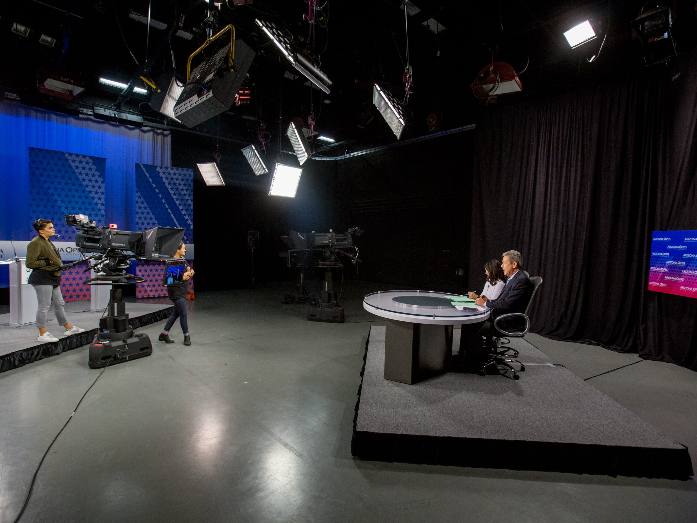 Crews and talent go through a debate opening on July 31, 2018, during a debate among Democrats vying for Arizona governor at Arizona State University's Walter Cronkite School of Journalism in Phoenix, Arizona.