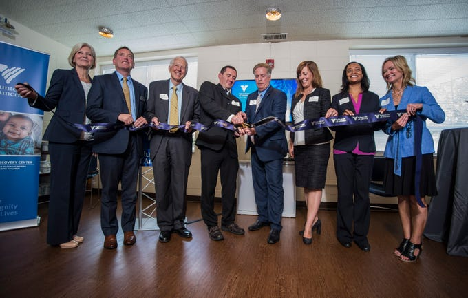 Winchester Mayor Shon Byrum cuts a ceremonial ribbon following a news conference celebrating the opening of the Winchester House, a new drug treatment facility for women, in Winchester, Ind., on Wednesday, Aug. 1, 2018.